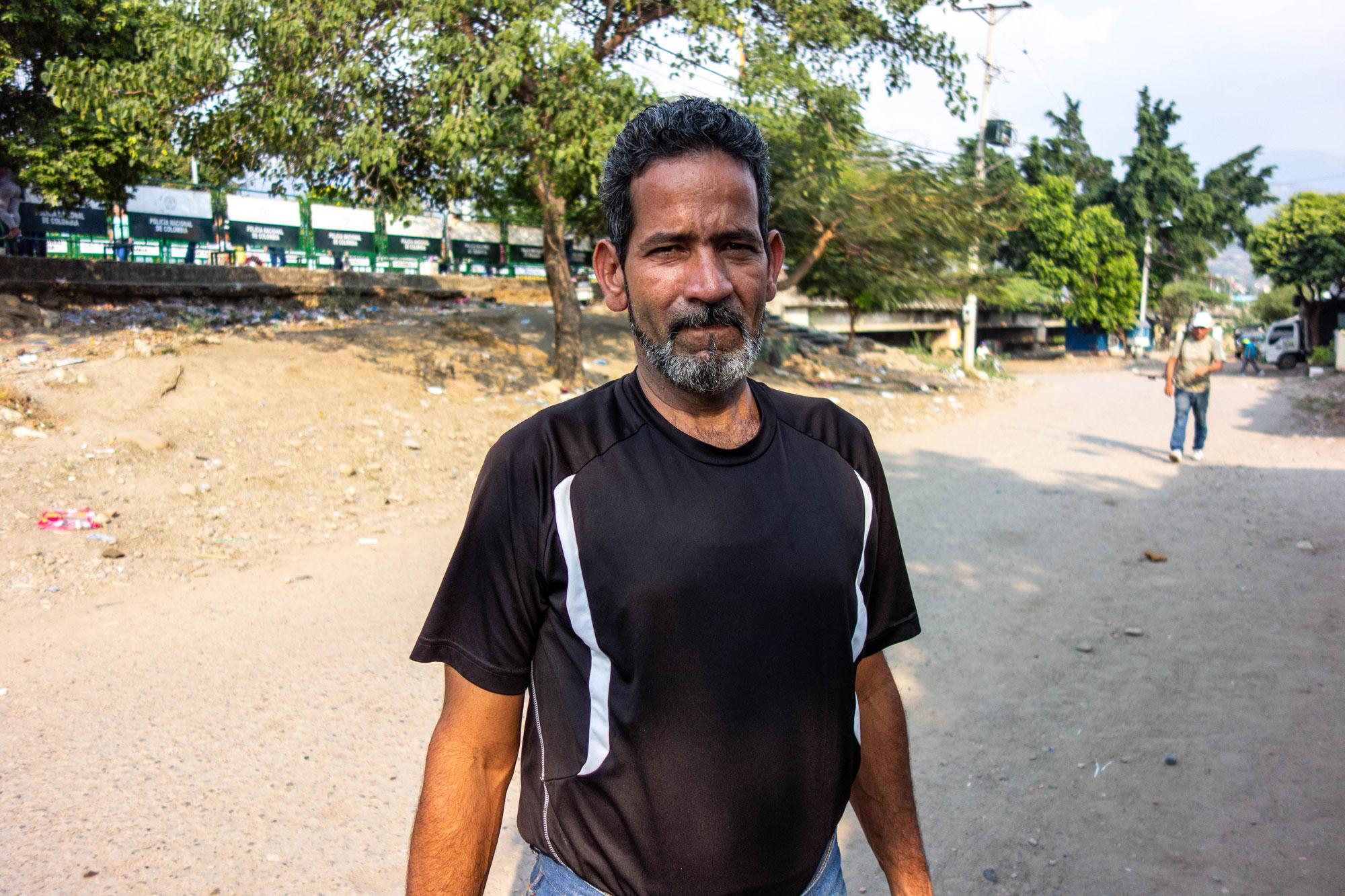 An older man wears a black shirt.