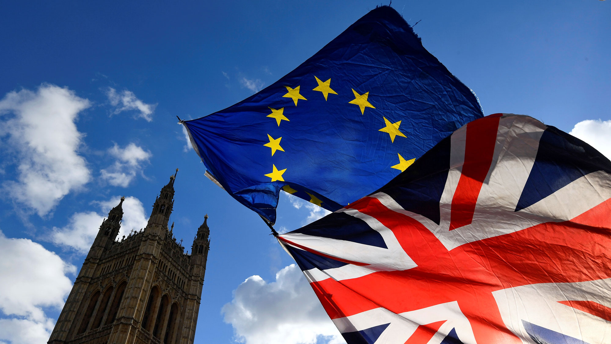 British and EU  are shown flying on the same line with the Houses of Parliament in London in the background.