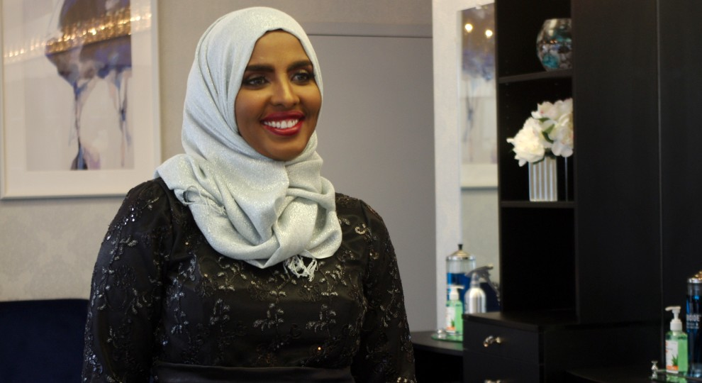 Shamso Ahmed smiles with red lipstick and a white hijab