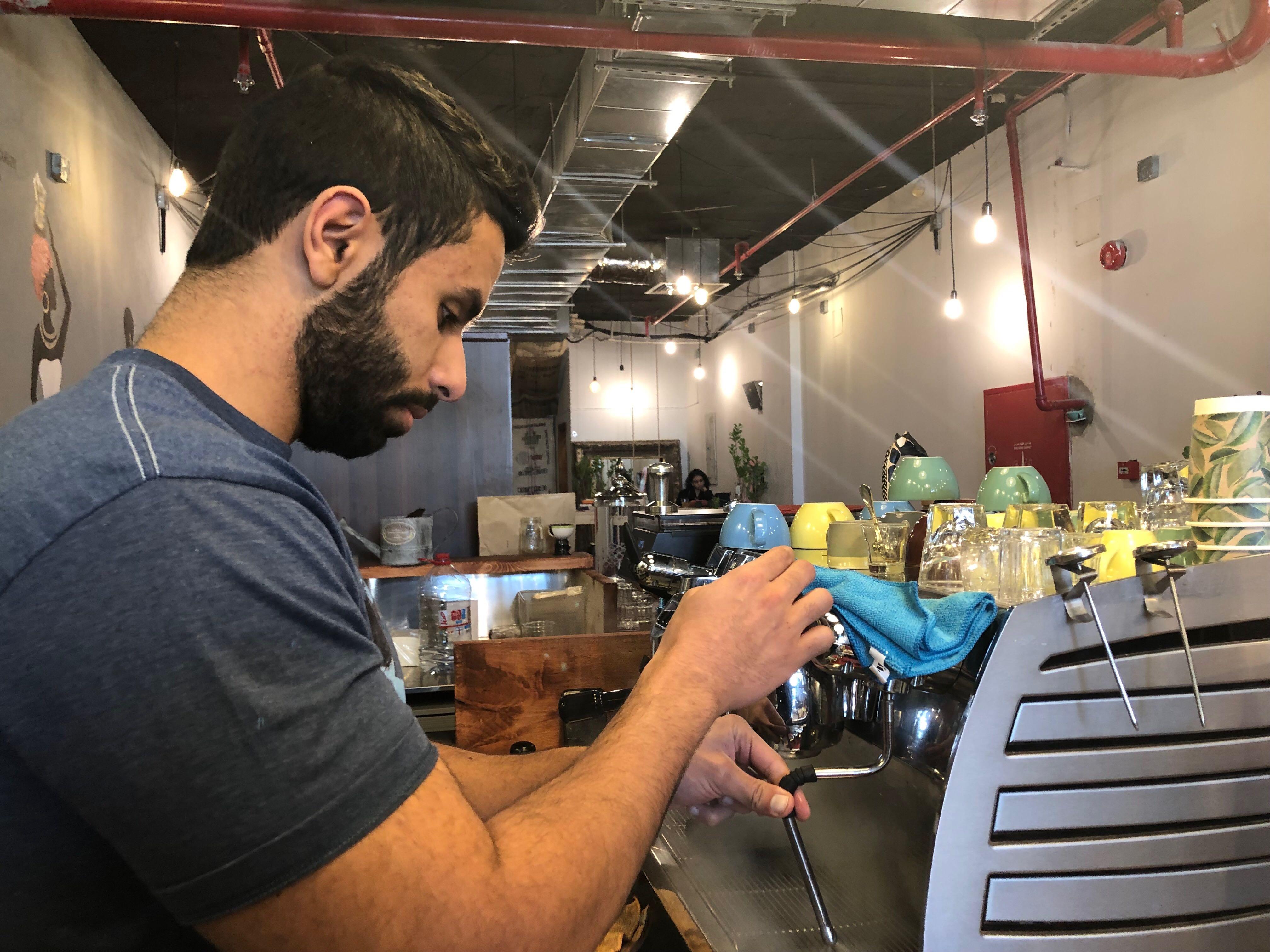 A beared man wearing a blue t-shirt works the espresso machine.