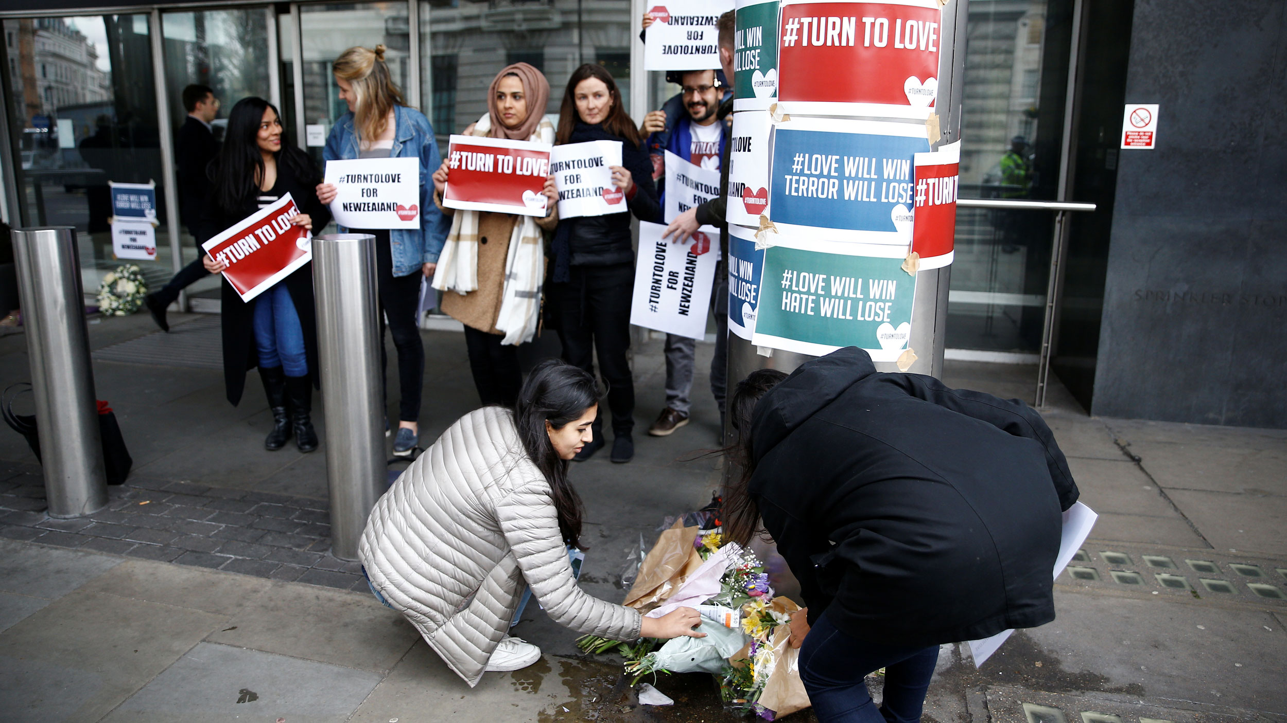 """A group of people leave flowers outside a building with signs table to a column that say """"#turntolove"""" and """"#love will win terror will lose"""""""