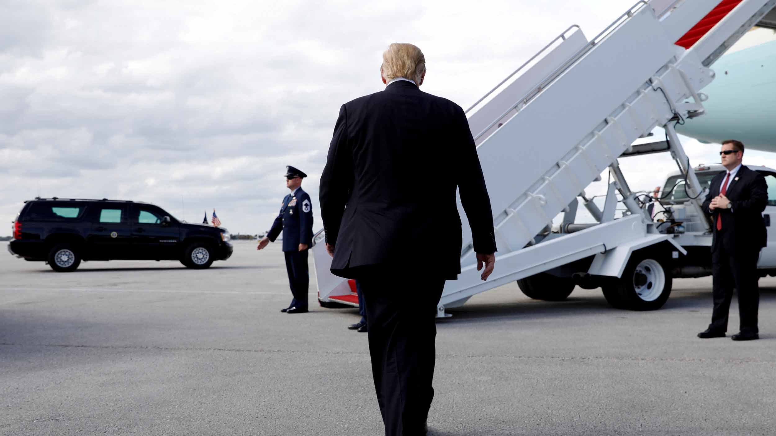US President Donald Trump walks toward steps leading to an airplane