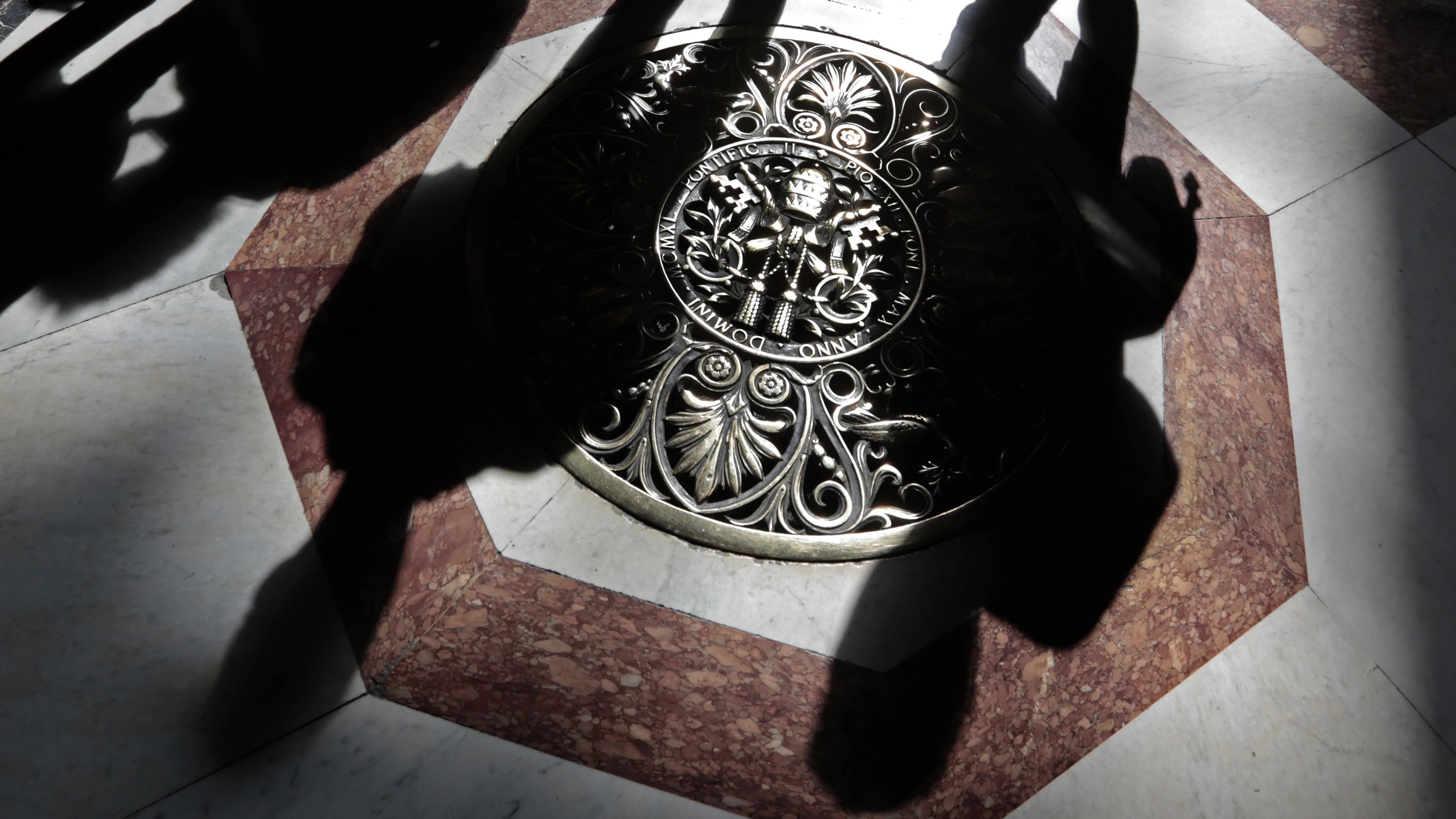 Shadows of tourists are cast across a papal crest on the floor