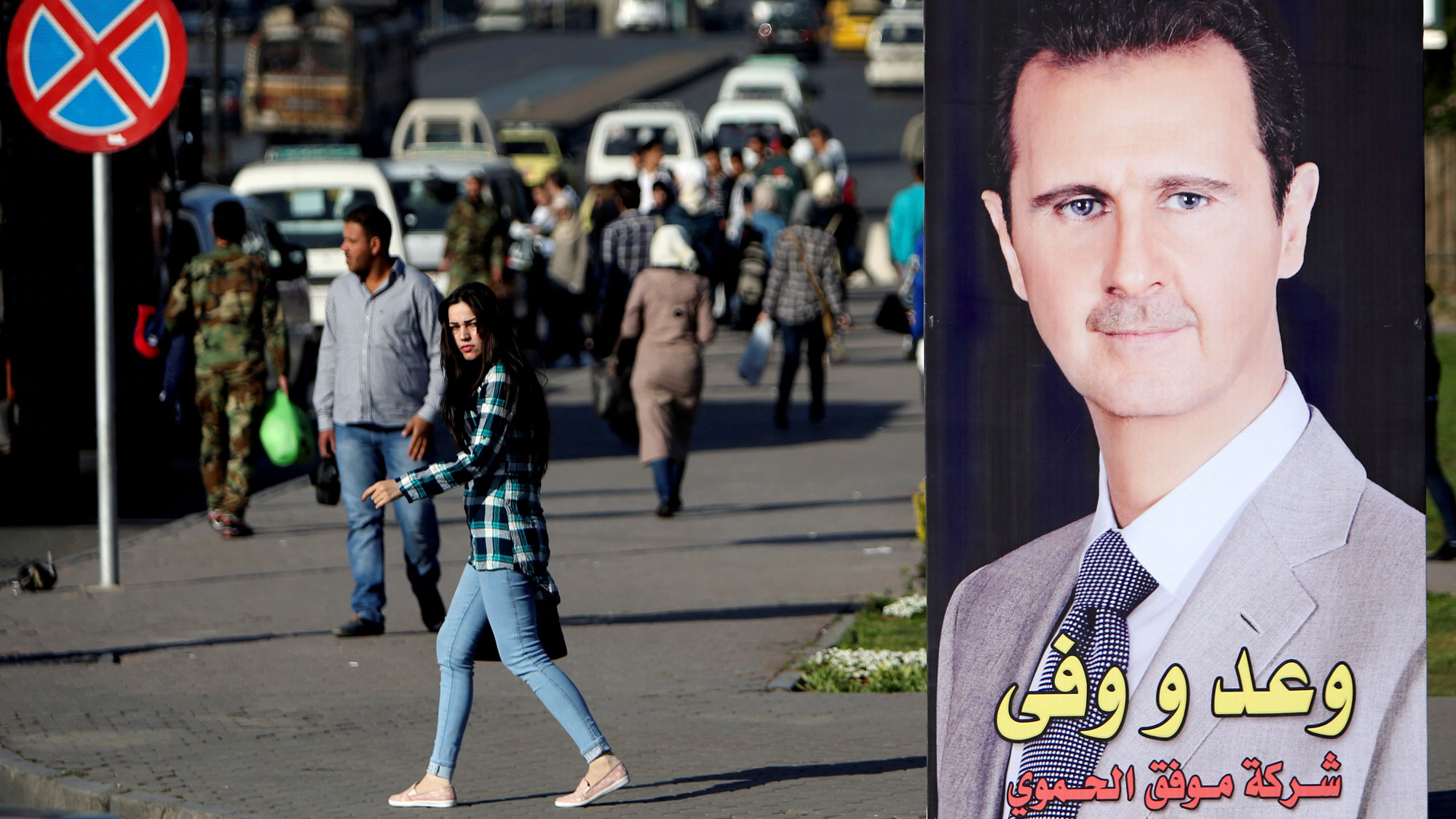 A woman walks wearing jeans and a plaid shirt is shown near a picture of Syrian President Bashar al-Assad in Damascus.
