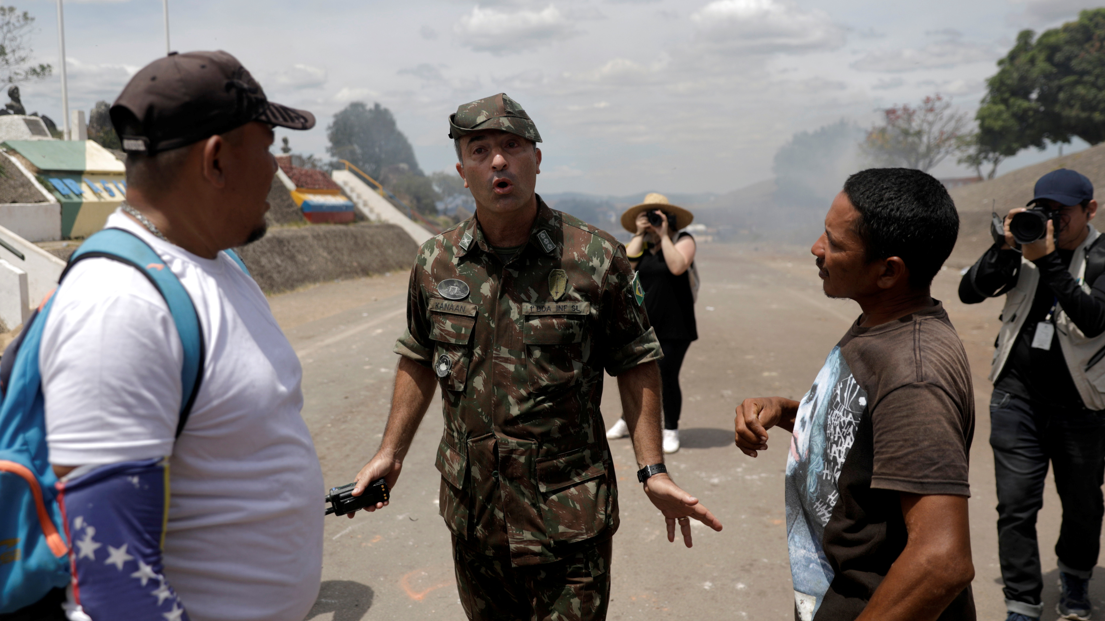 Man in uniform stands between two civilians with gesture of calm.