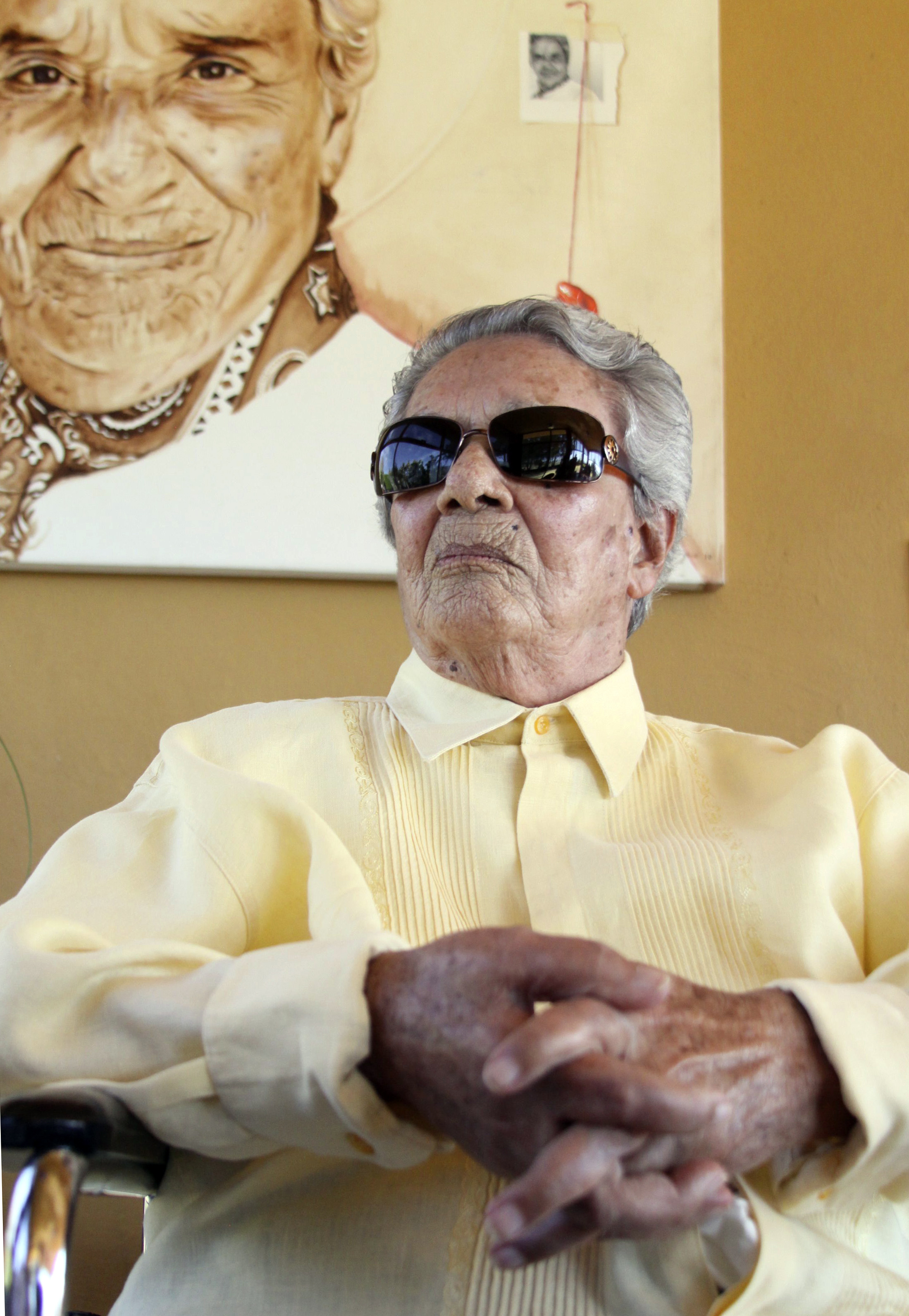 Chavela Vargas wears a yellow blouse and sunglasses and sits in front of a her painted portrait.