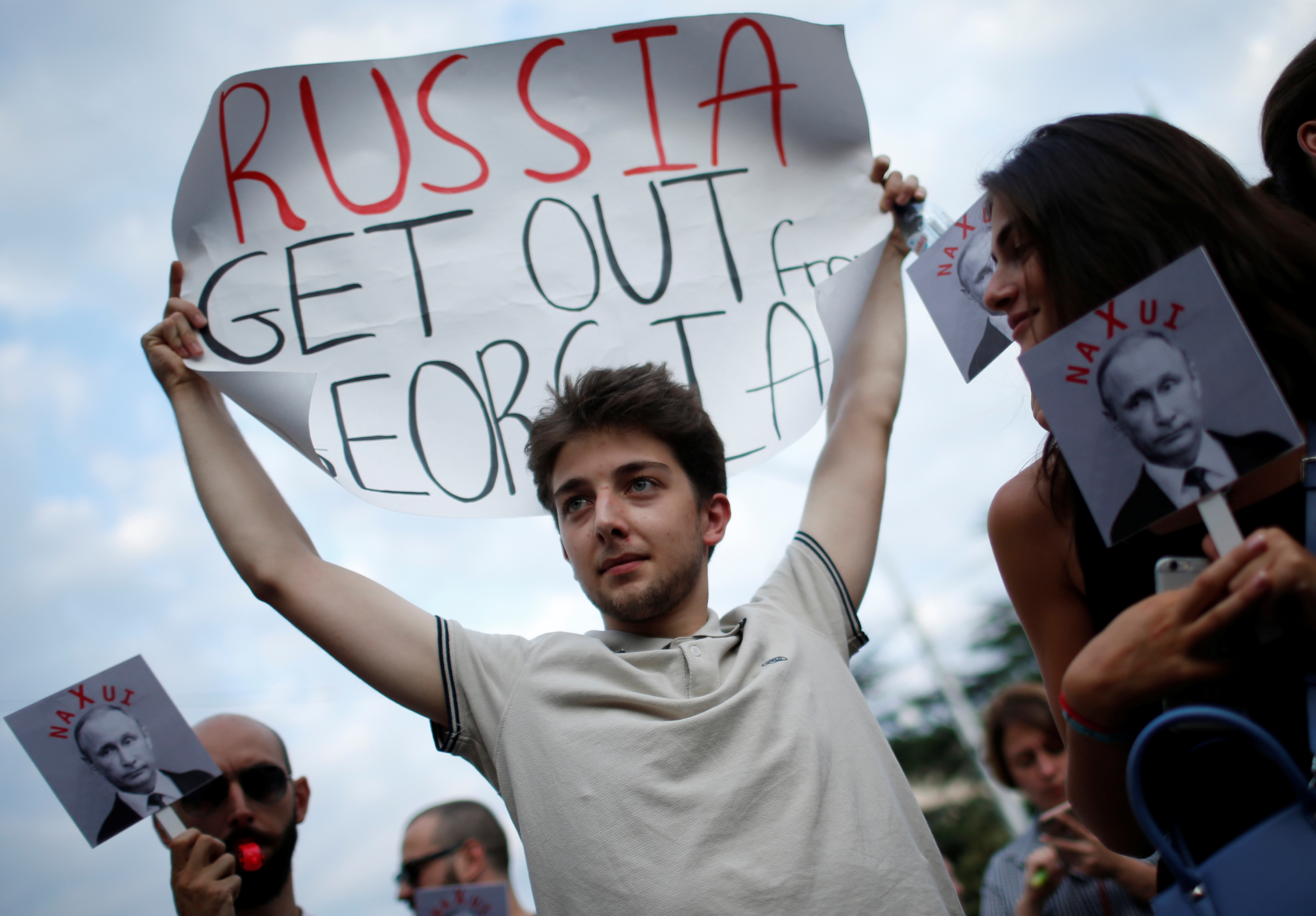 """A man in a crowd wearing a white T-shirt holds up a sign saying 'Russia get out of Georgia."""""""