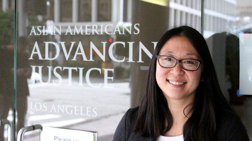 A woman with glasses stands in front of an office front with the sign Asian Americans Advancing Justice Los Angeles