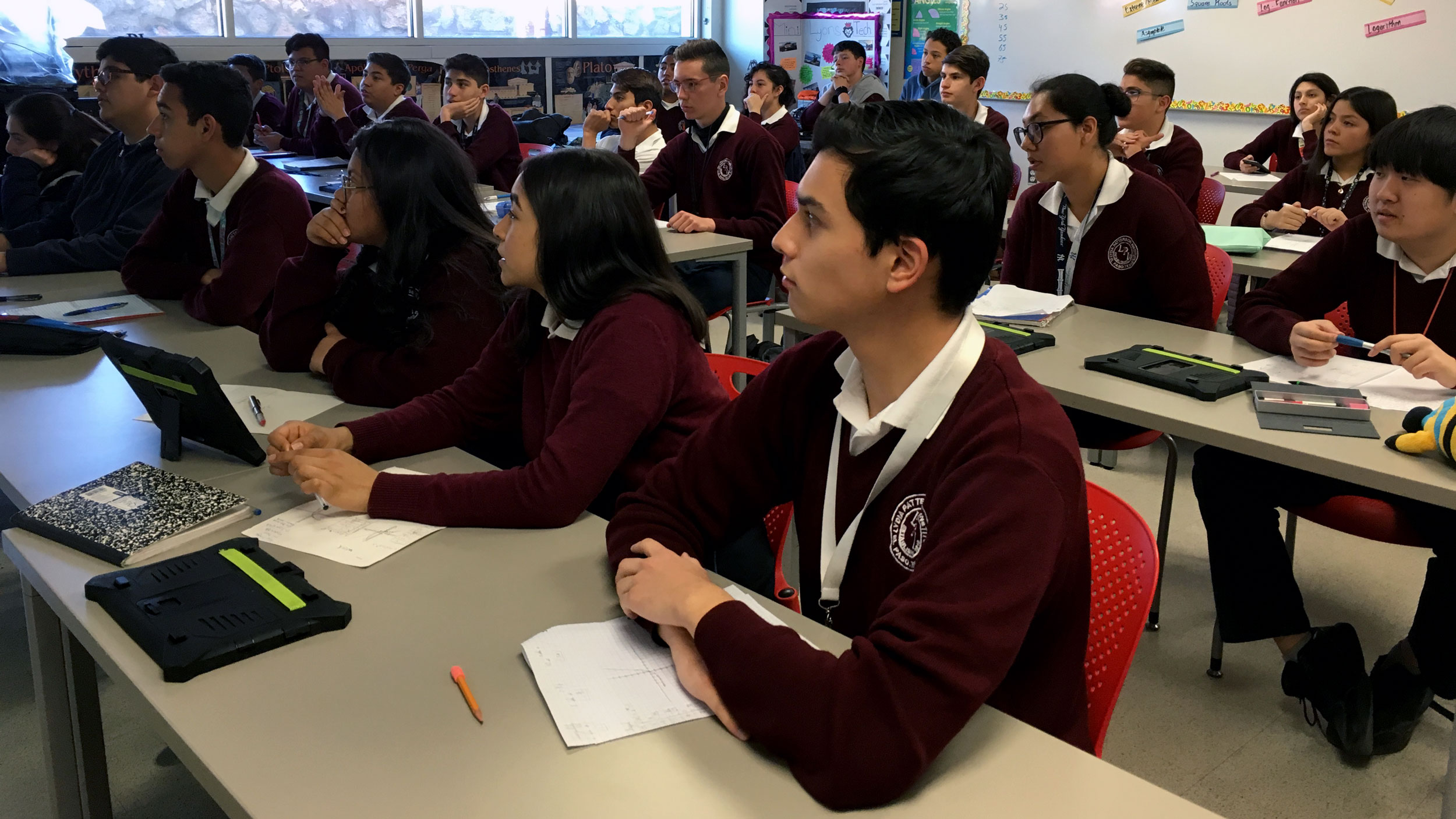 Students in maroon uniforms sit at desks and listen to a teacher, not pictured