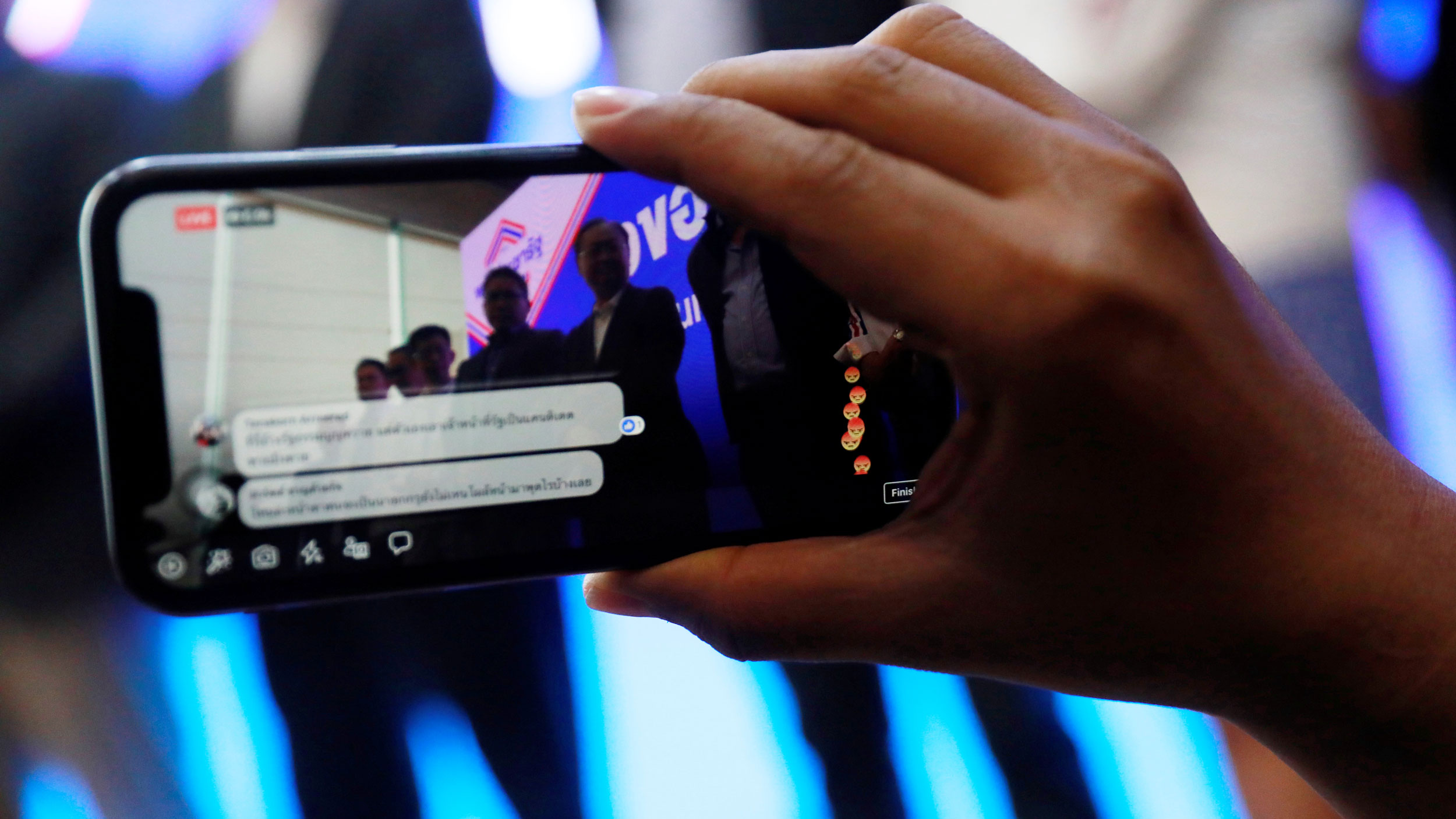 A hand holds a cell phone that is playing a facebook live video and angry faces are showing up in the bottom right corner