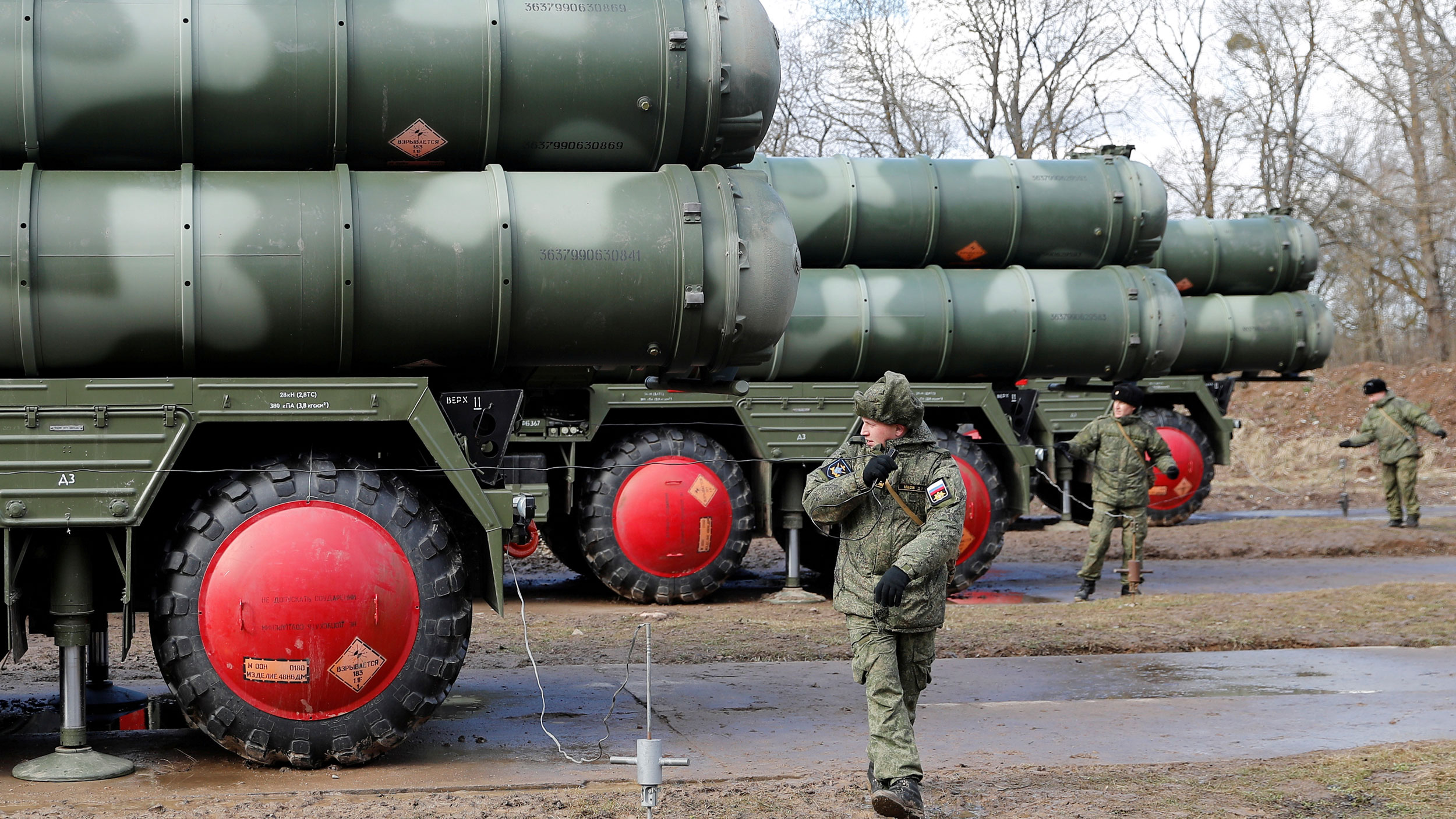 Russian servicemen dressed in fatigues stand next to a large trucks with surface-to-air missile system on top.
