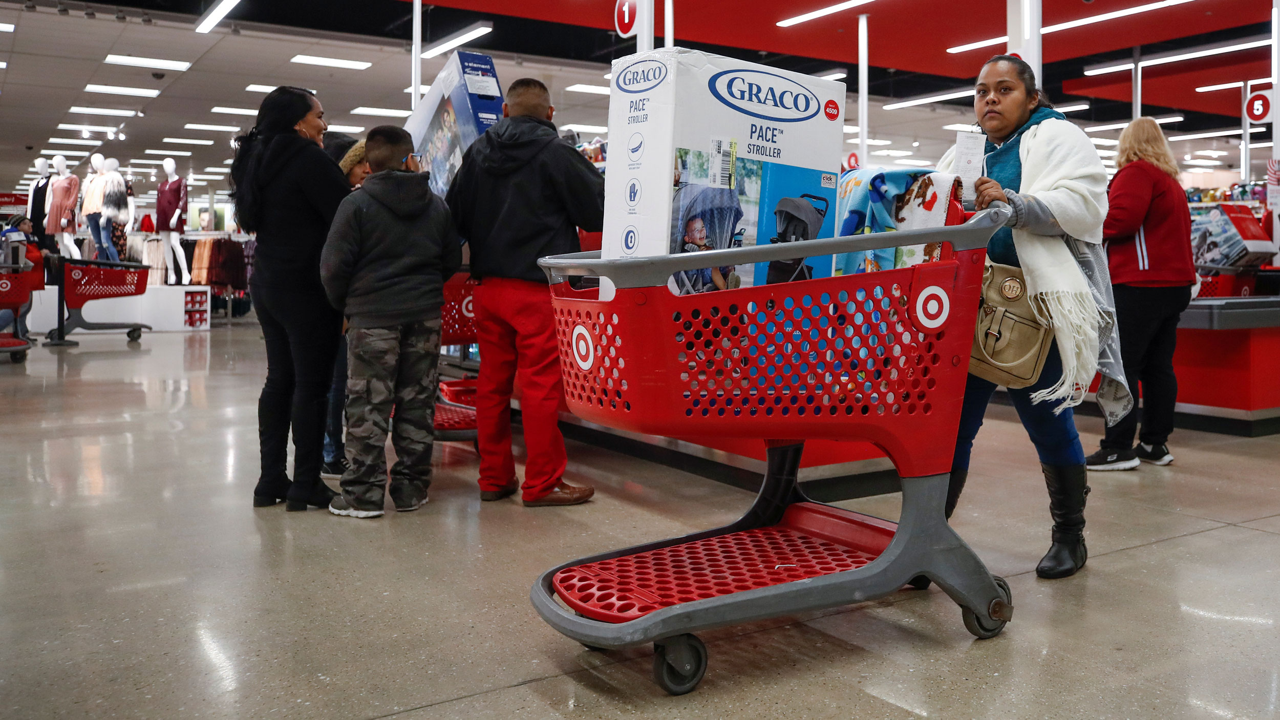 A customer pushes her shopping cart, filled with Chinese-made products, after making a purchase at a Target in Chicago, Illinois.