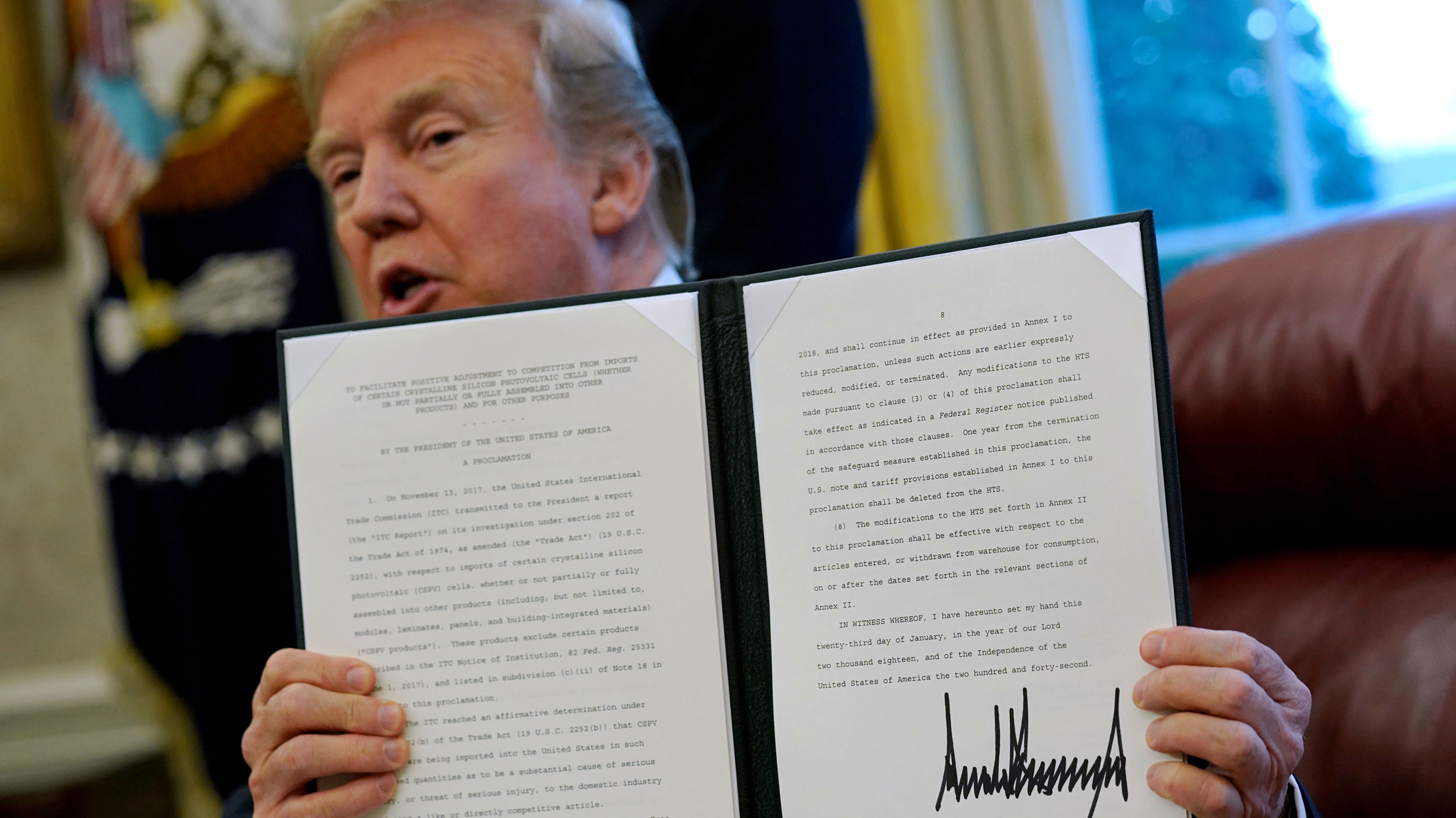Donald Trump is shown holding.a folder with a directive typed out and his signature.