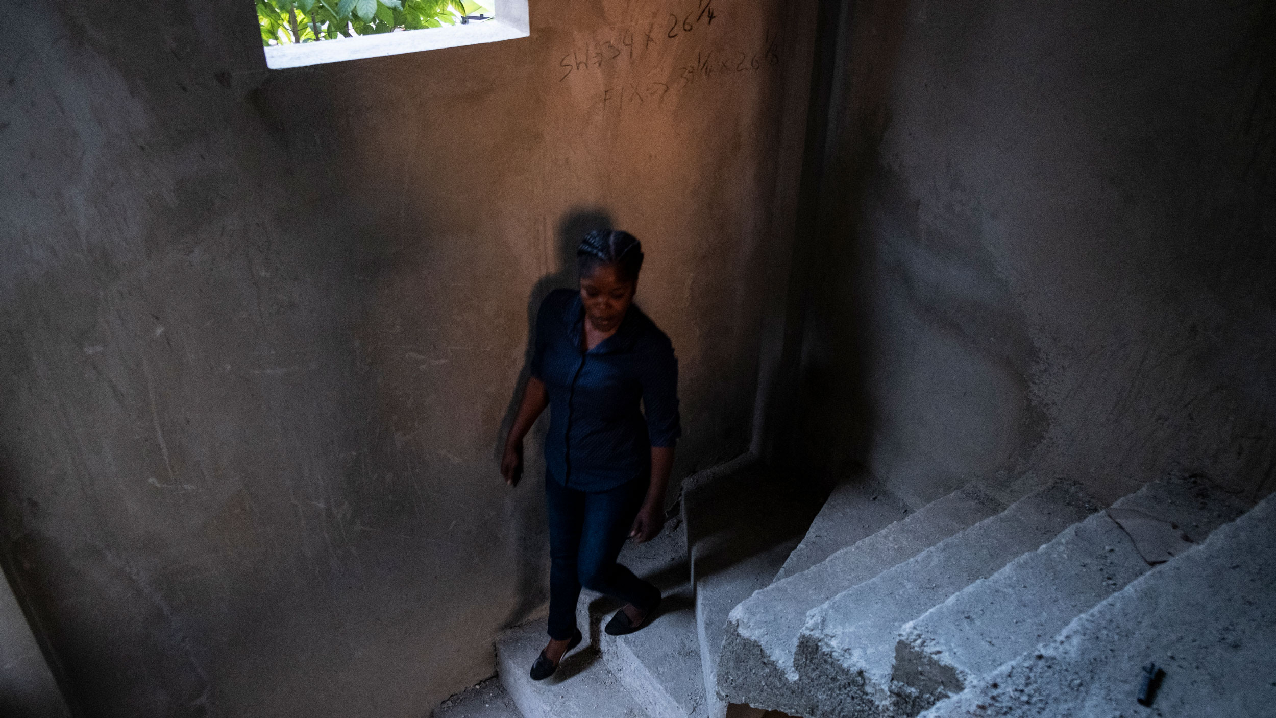 A woman is shown walking down a cement staircase in Port-au-Prince, Haiti.