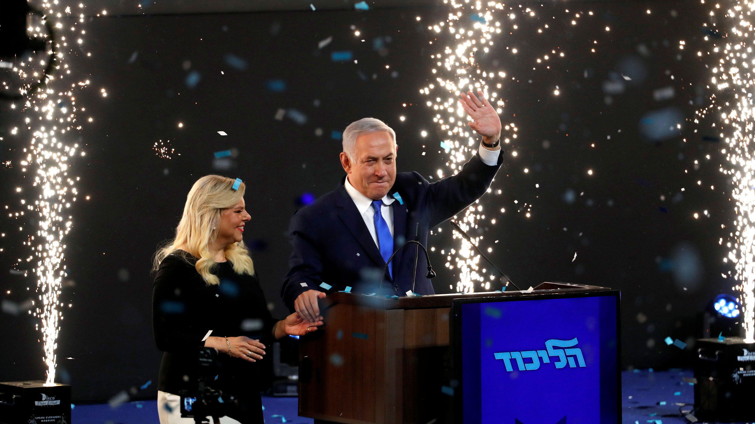 Confetti is shown falling falling with sparkling fireworks shooting up with Israeli Prime Minister Benjamin Netanyahu and his wife Sara standing on stage.