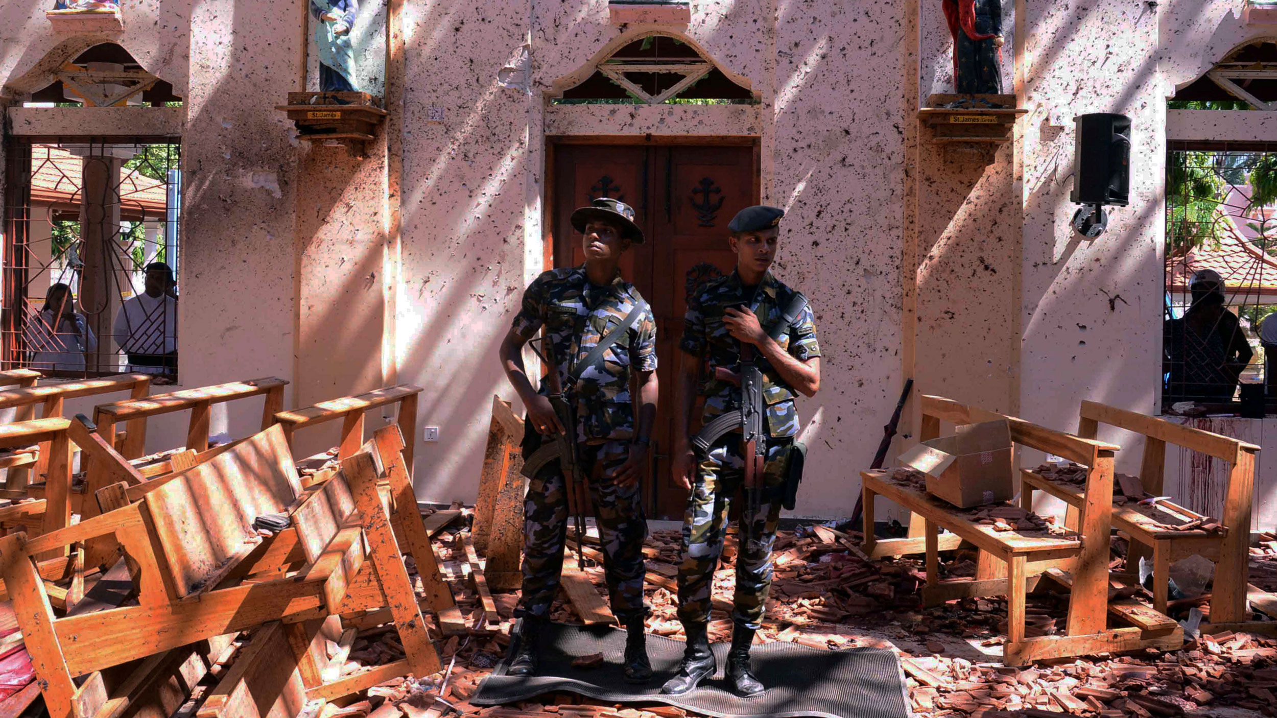 Two Sri Lankan military are shown standing with weapons over their shoulders in front of a church after an explosion.