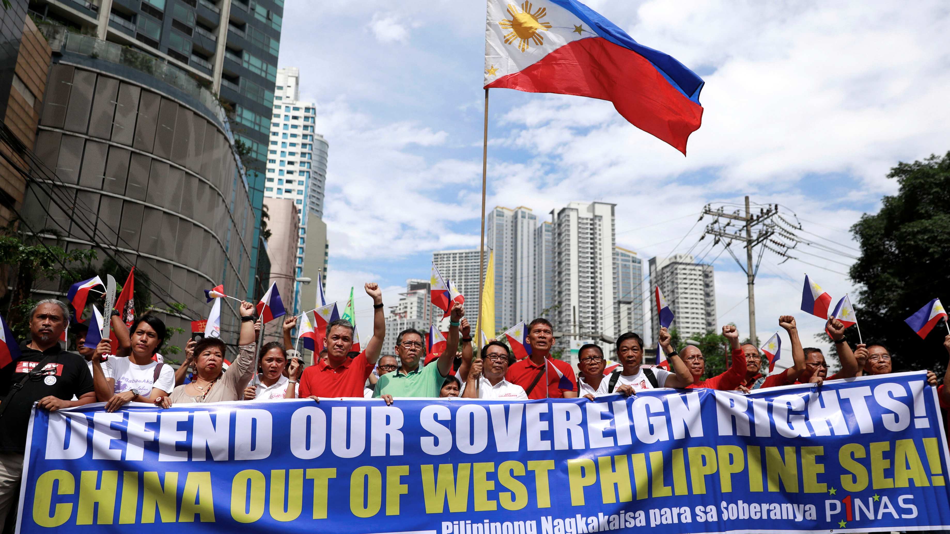 protesters carry blue and red signs saying 'defend our sovereignty'