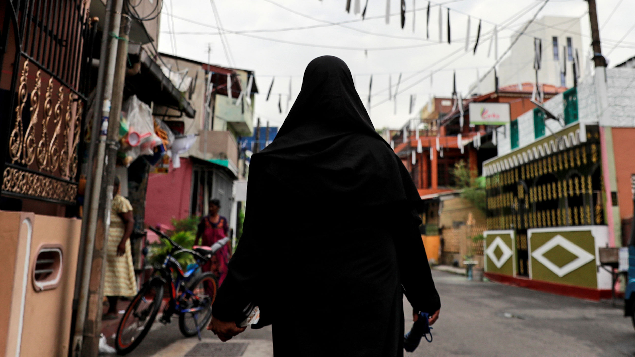A woman is shown from behind wearing a black hijab walking through the middle of a street.