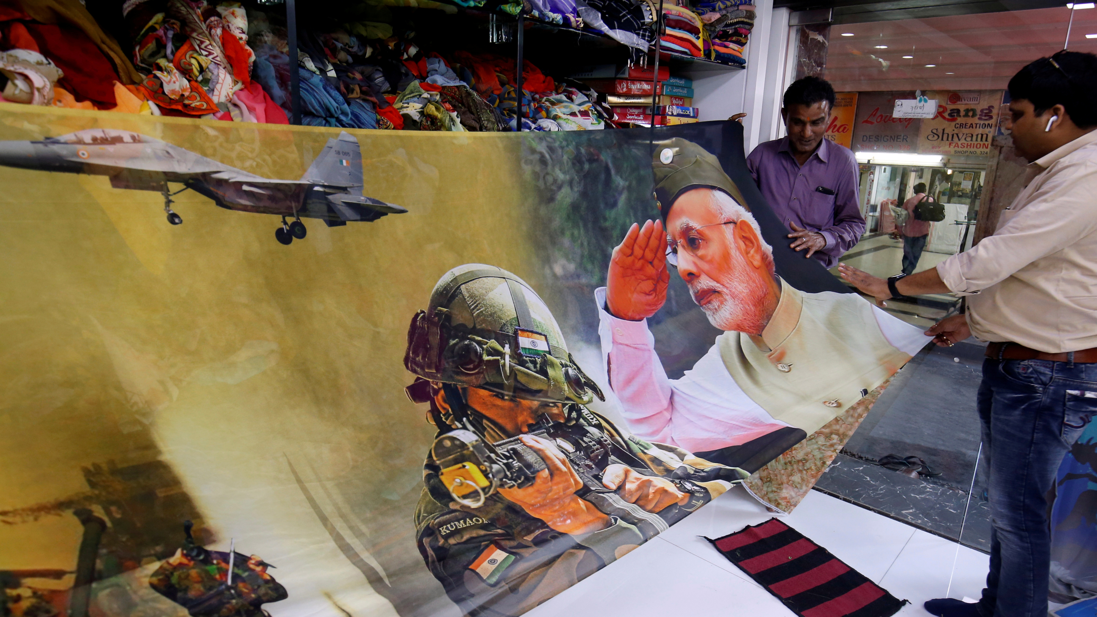 Trader displays sari with image of modi with his military tanks