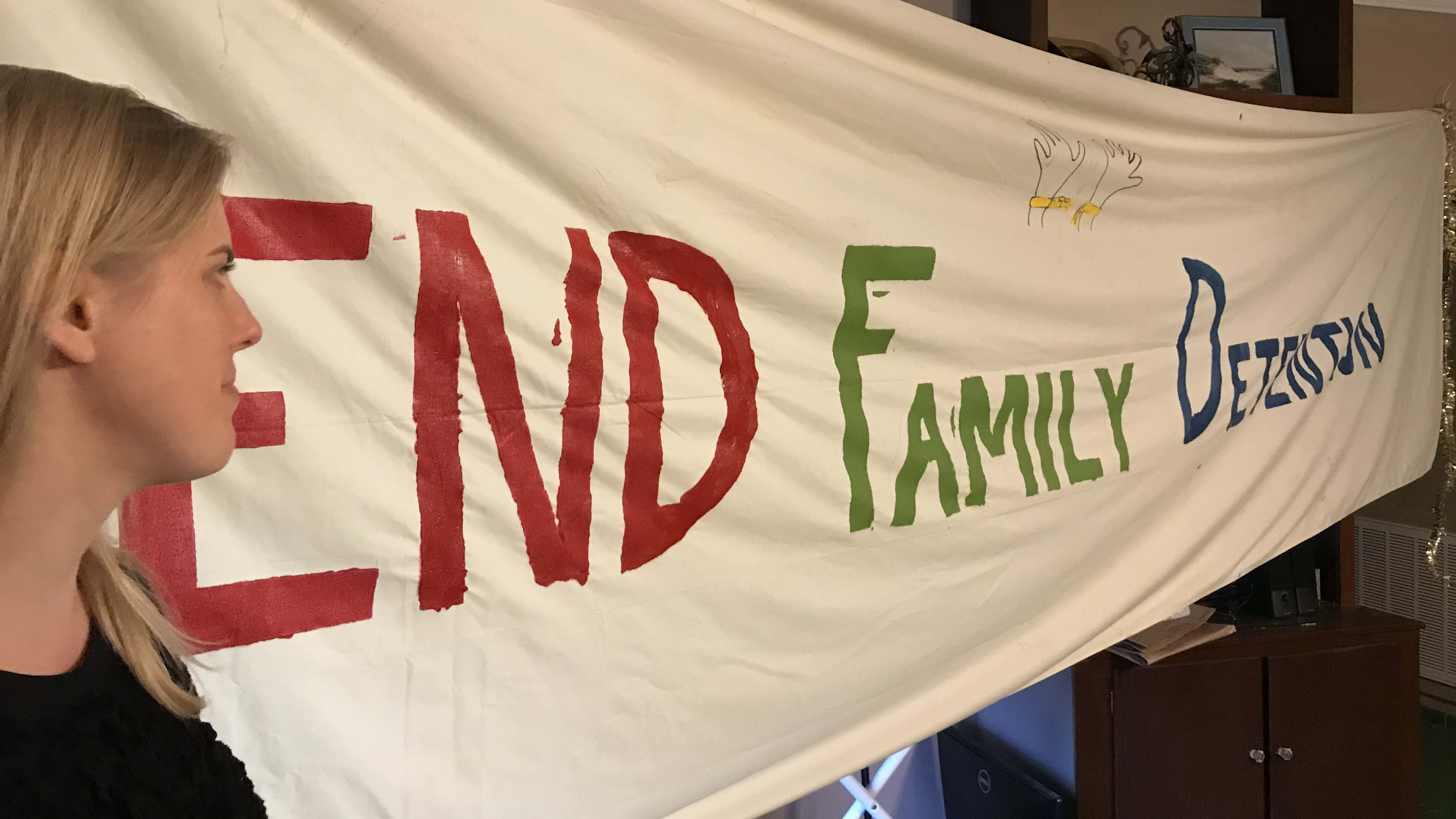 """A woman stands in front of a banner reading """"End Family Detention"""""""