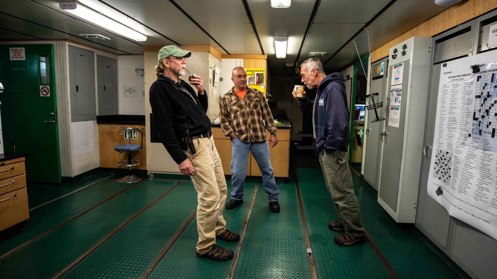 Three crew members are shown in a room with a green floor all leaning in order to stay balanced.