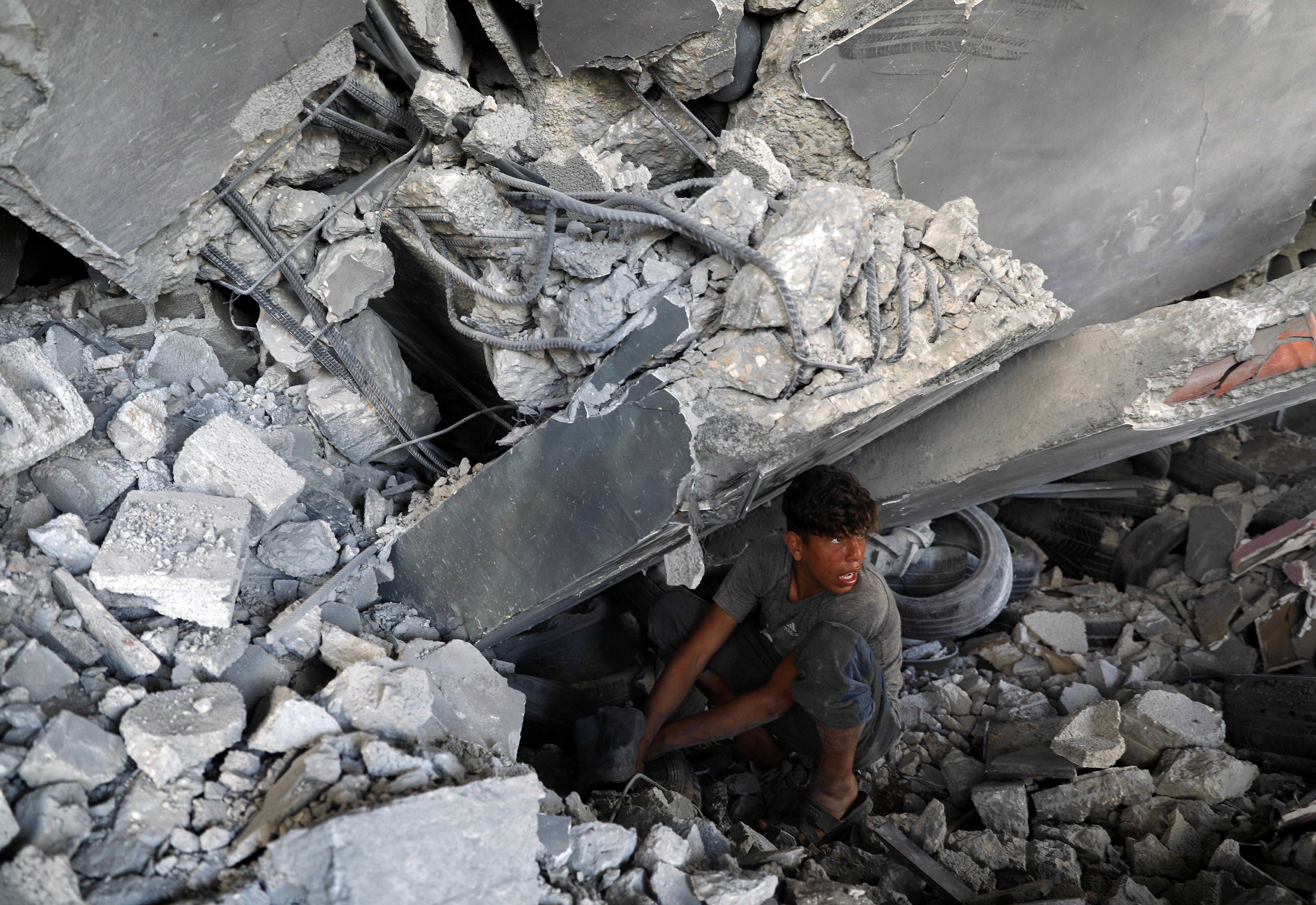 A boy squats in building rubble