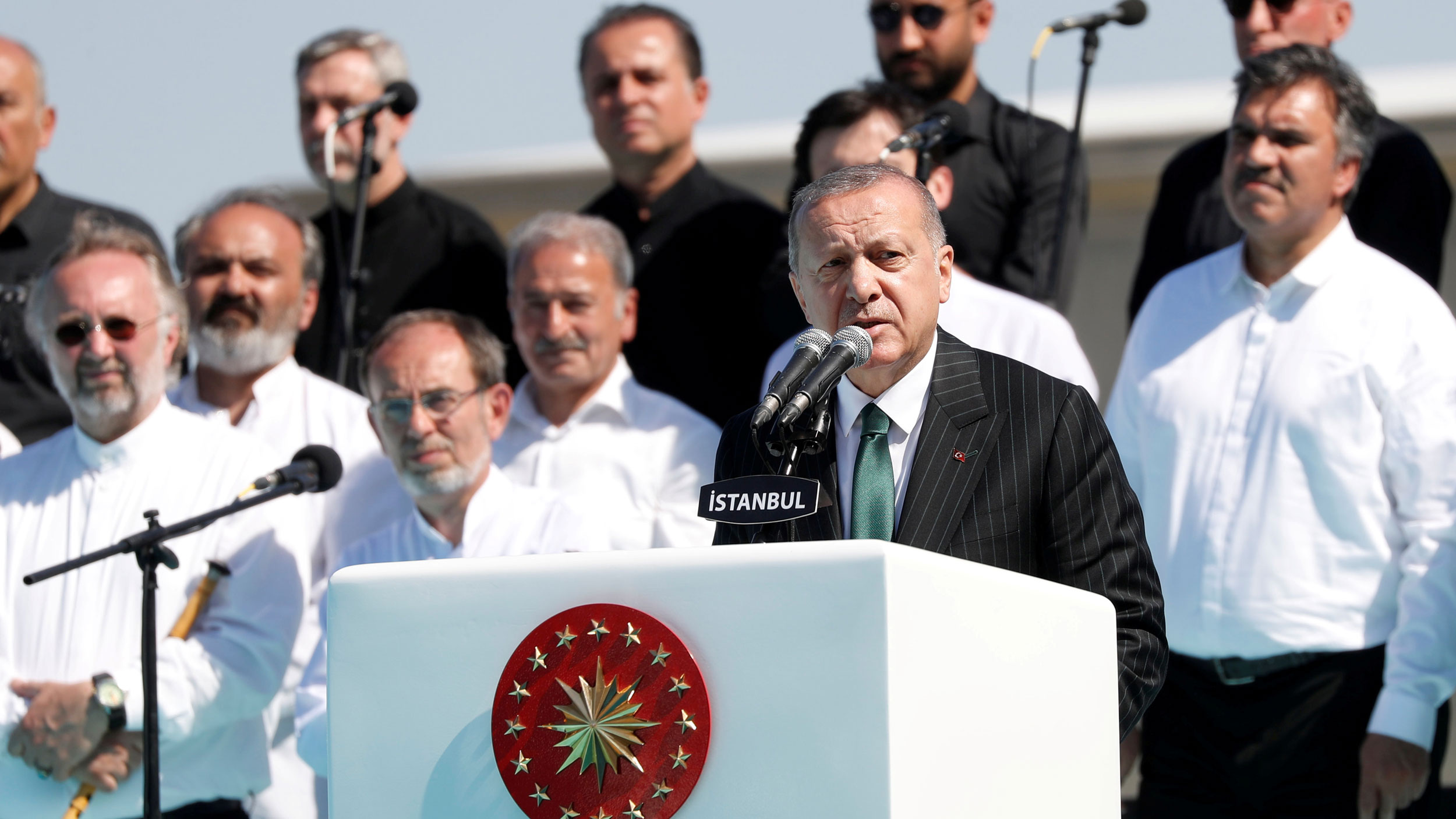 Turkish President Tayyip Erdoğan is shown making a speech behind a white podium with several stars on it.