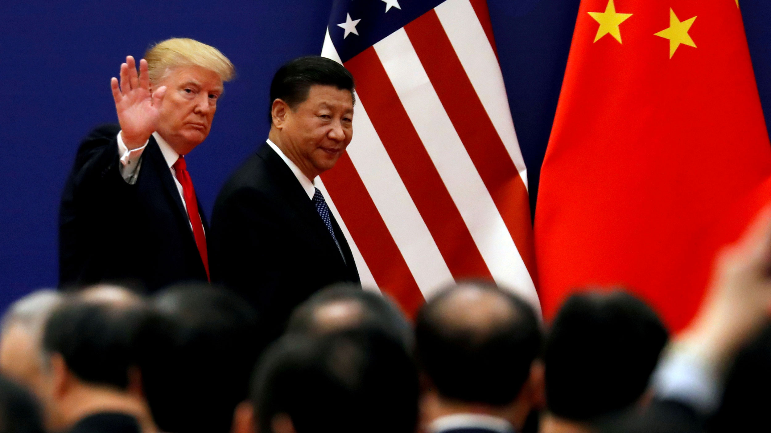 US President Donald Trump and China's President Xi Jinping are shown walking with the US and China flags in the background and Trump waving.