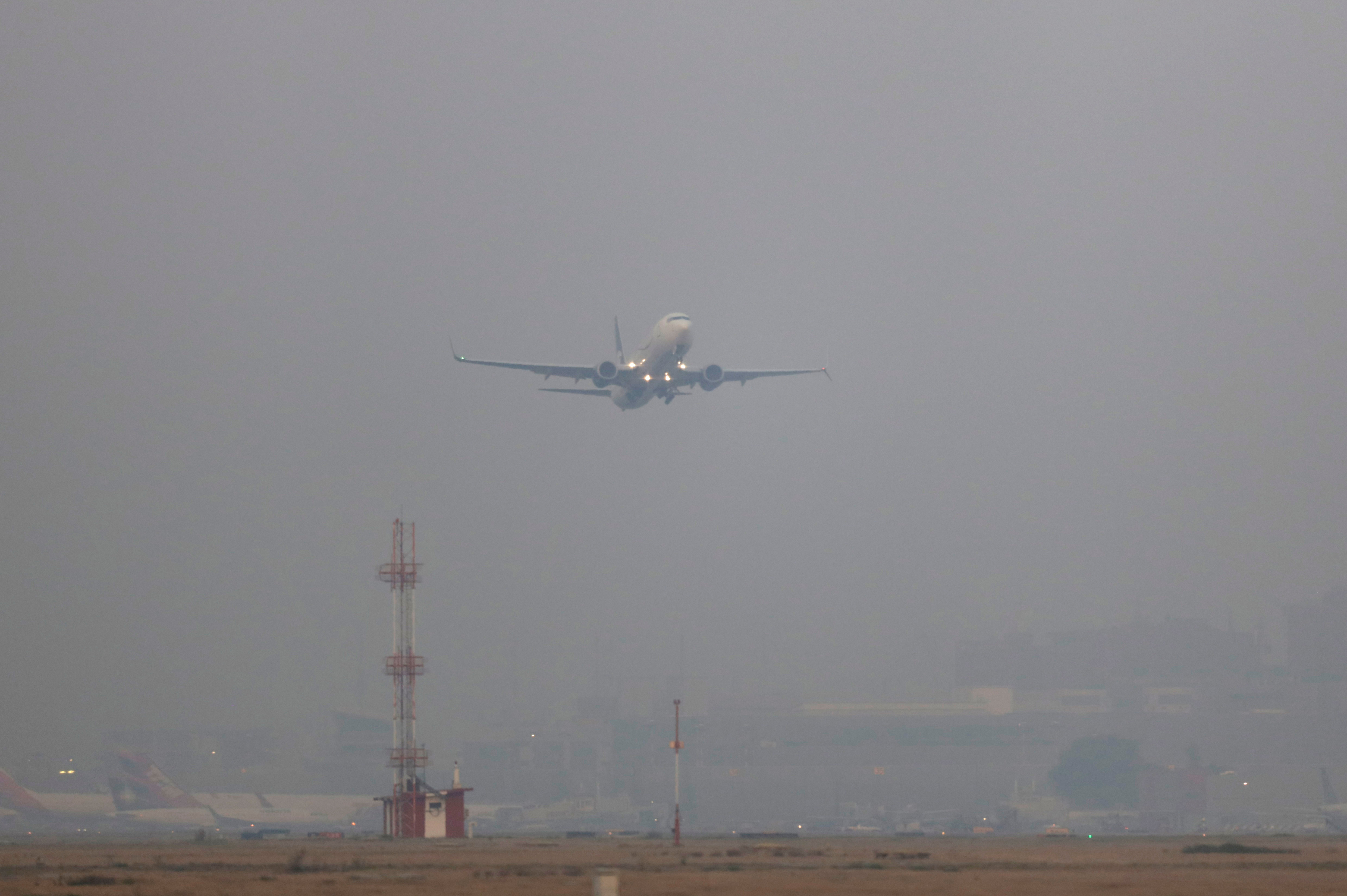 A plane takes off in smog