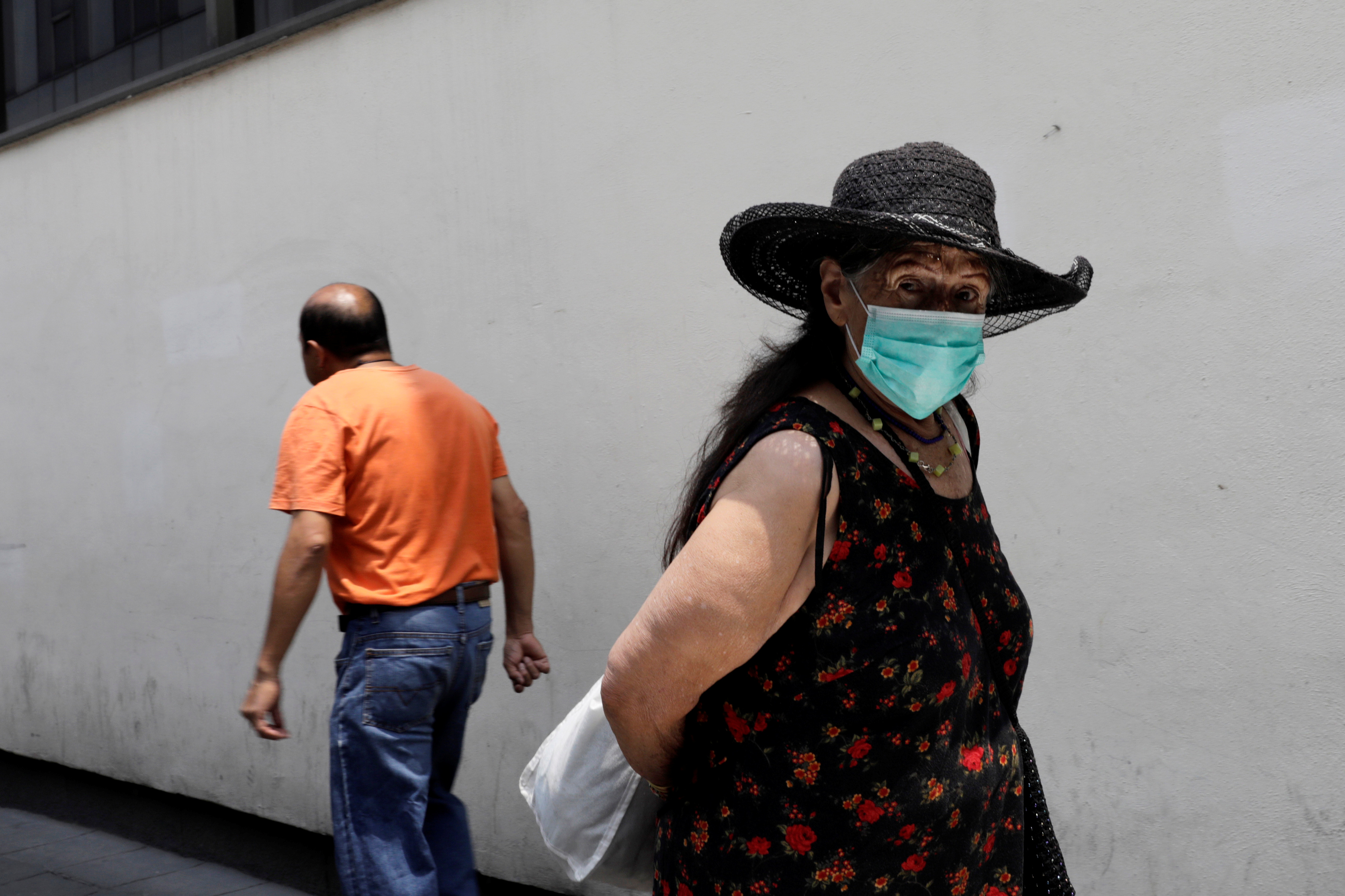 An older woman wears a surgical mask as she looks at the camera