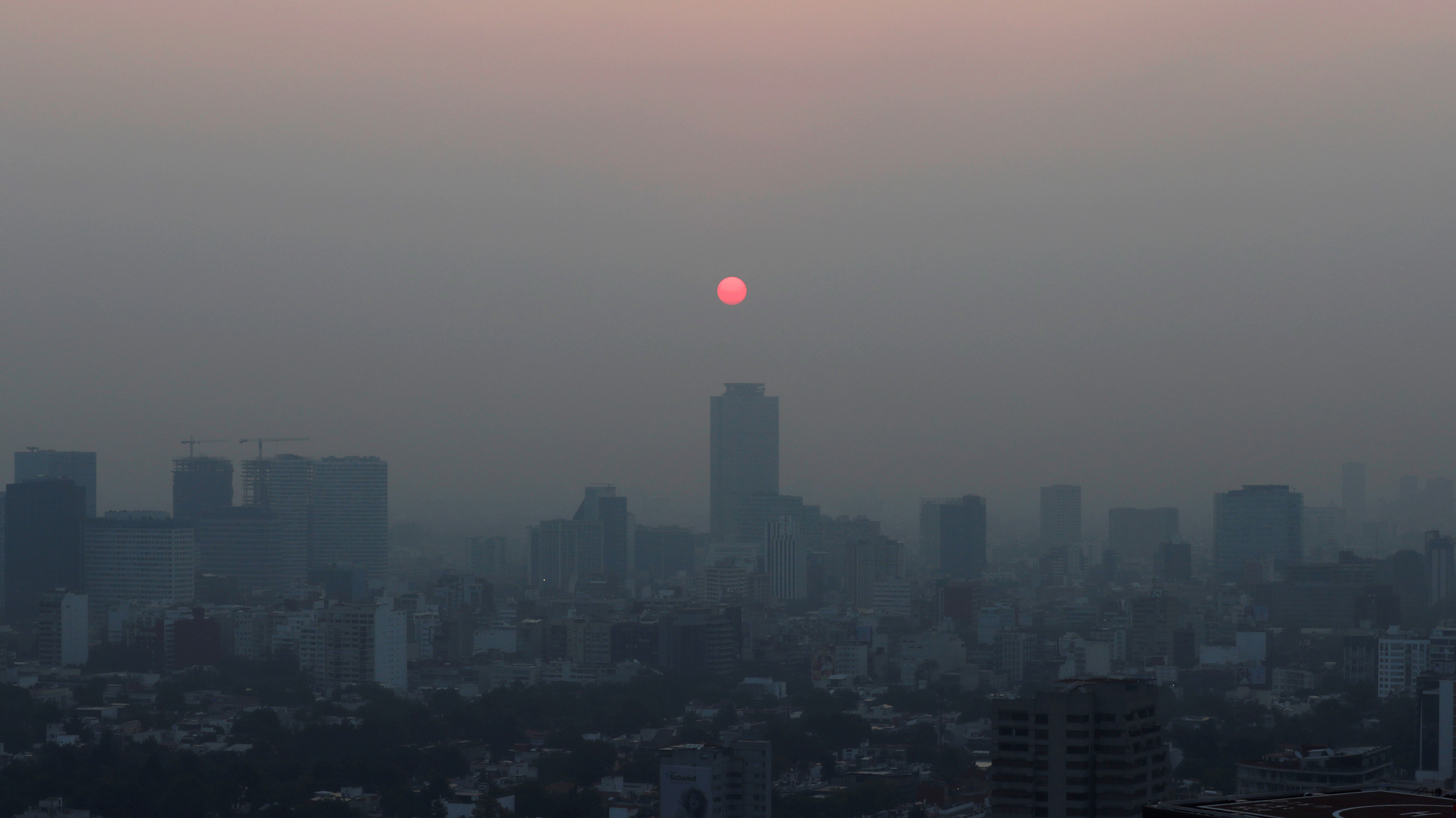 Buildings shrouded in smog with a red orb in the sky