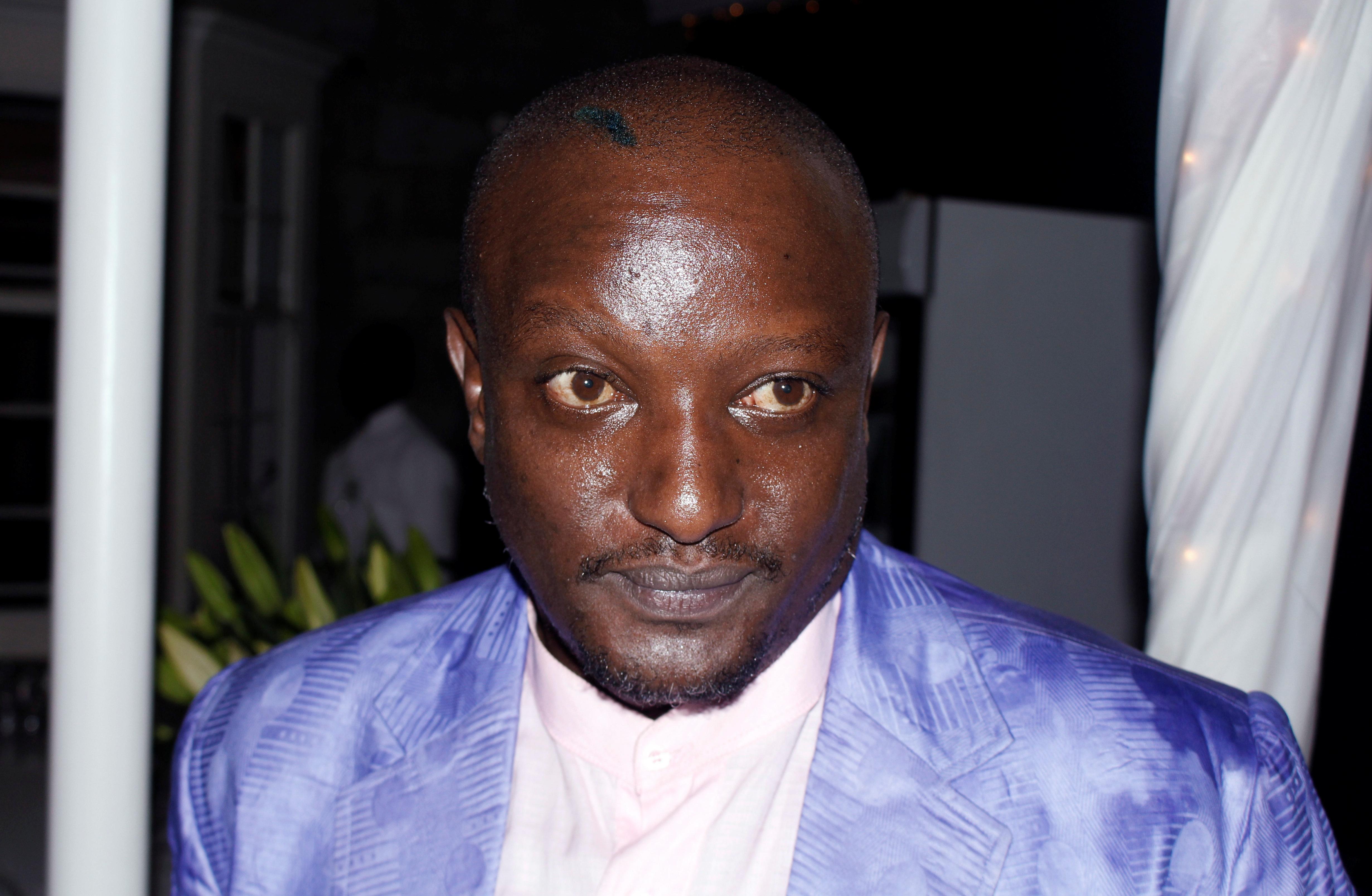 Portrait of the late Binyavanga Wainaina in shiny purple suit with white shirt