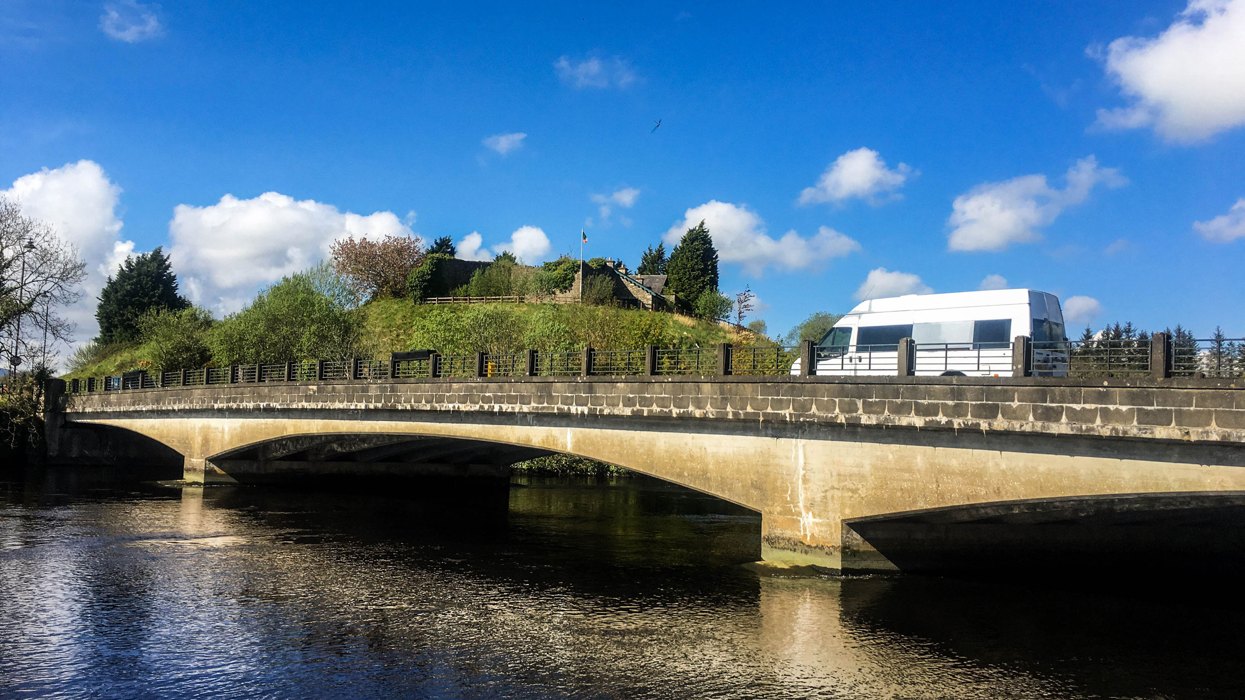 A white van travels over a grey stone bridge on a bright, sunny day under blue skies.