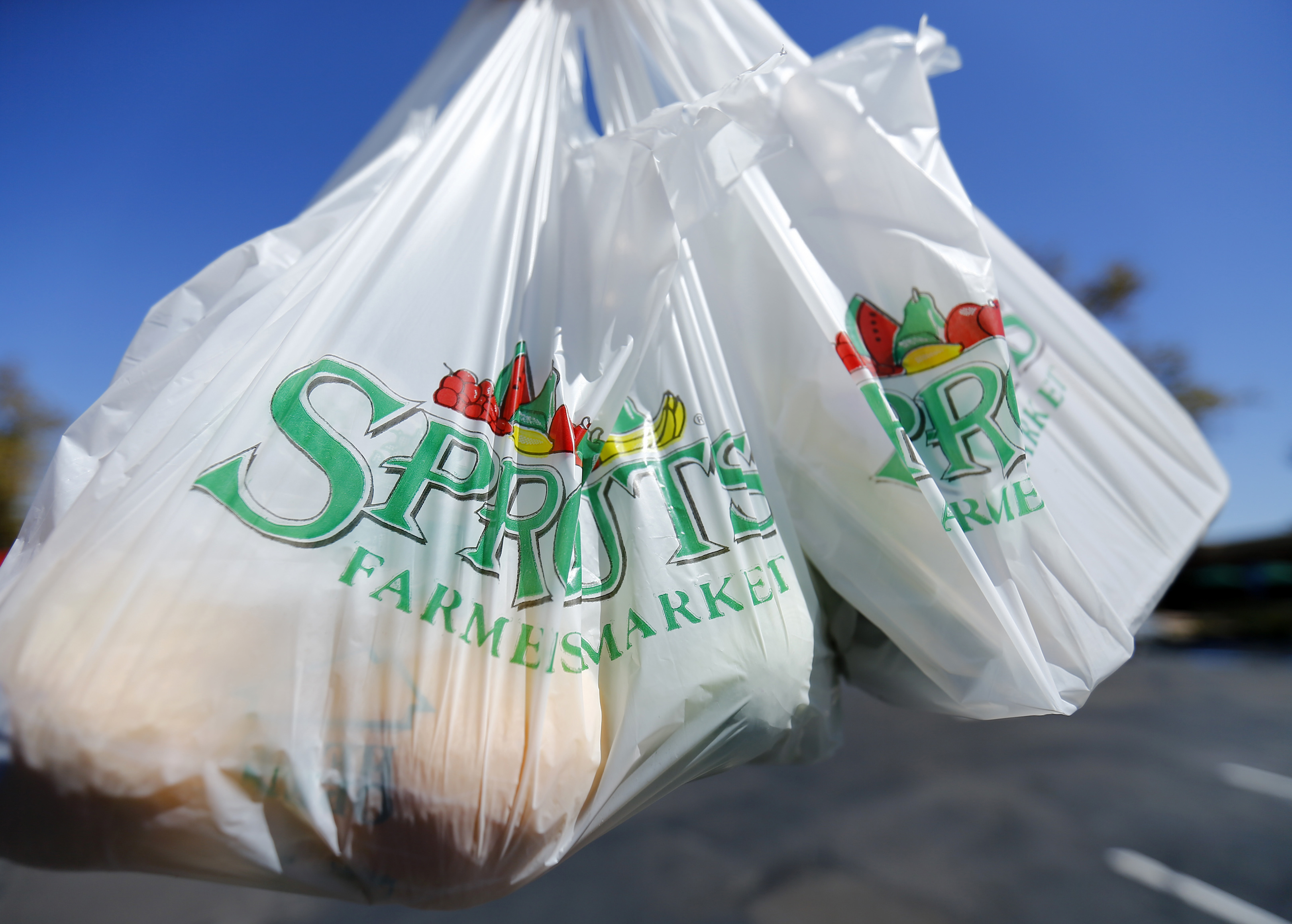 Two plastic grocery bags being held .