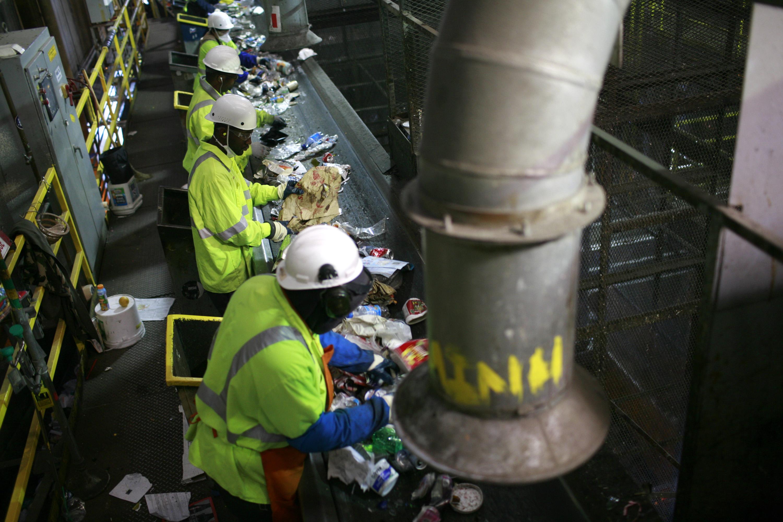 Workers in a dark building sort trash from a conveyor belt.
