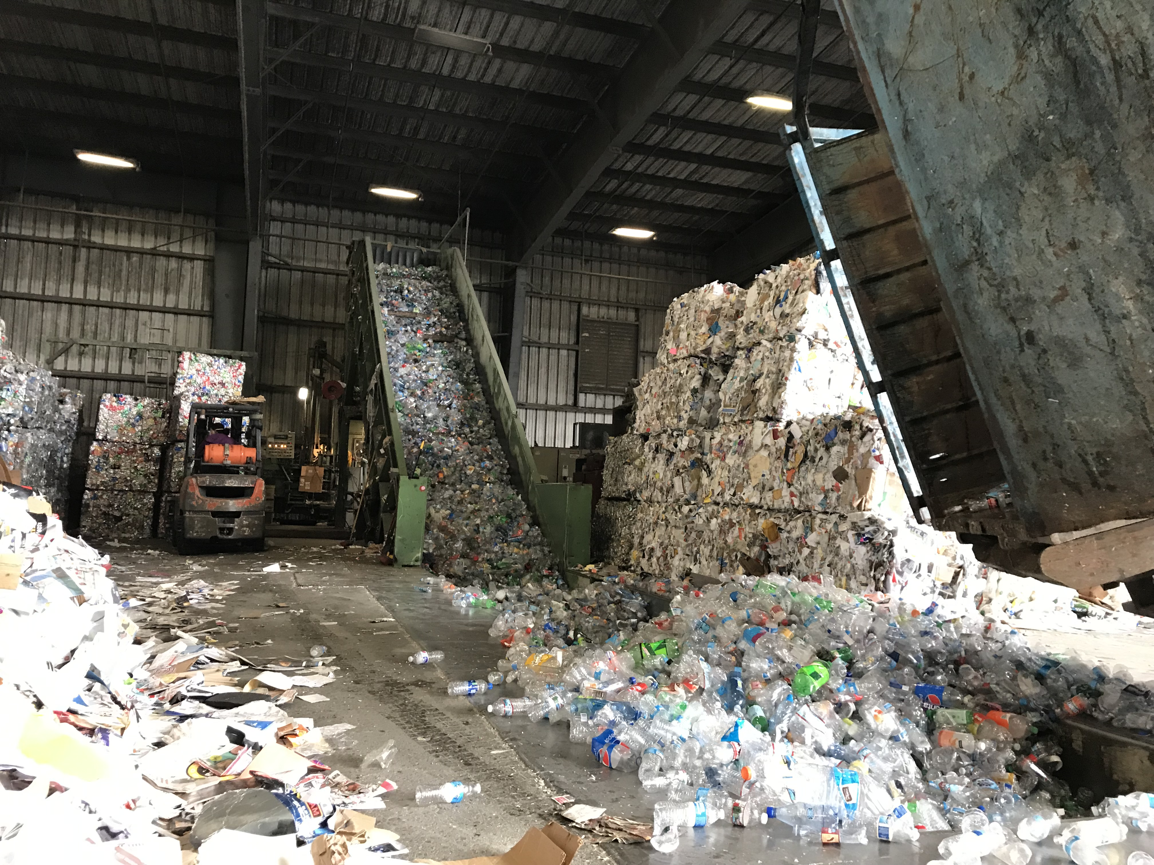 Large collections of plastic are spread out and sorted inside a warehouse.