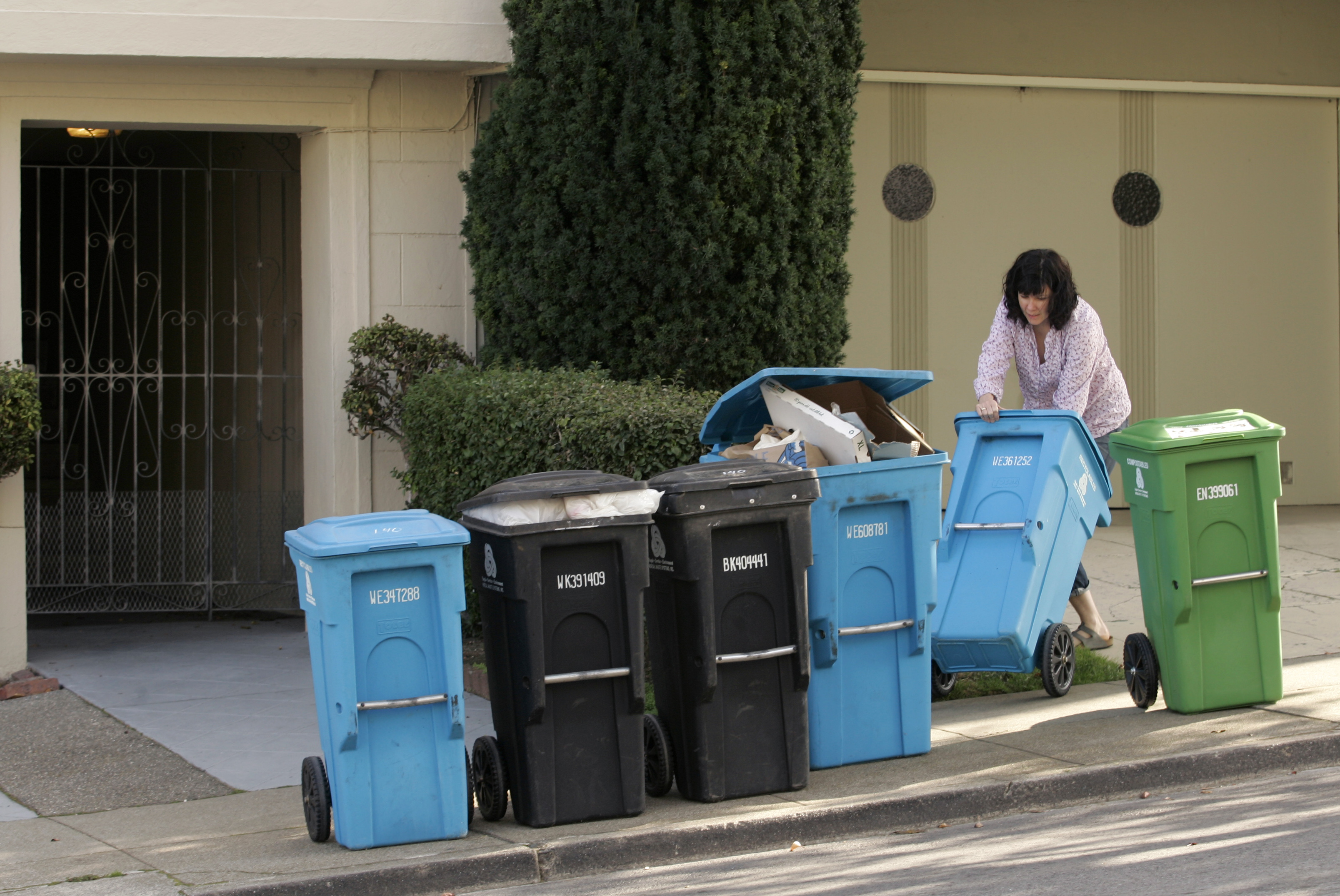 A woman puts different large garbage and recycling containers on a sidewalk.