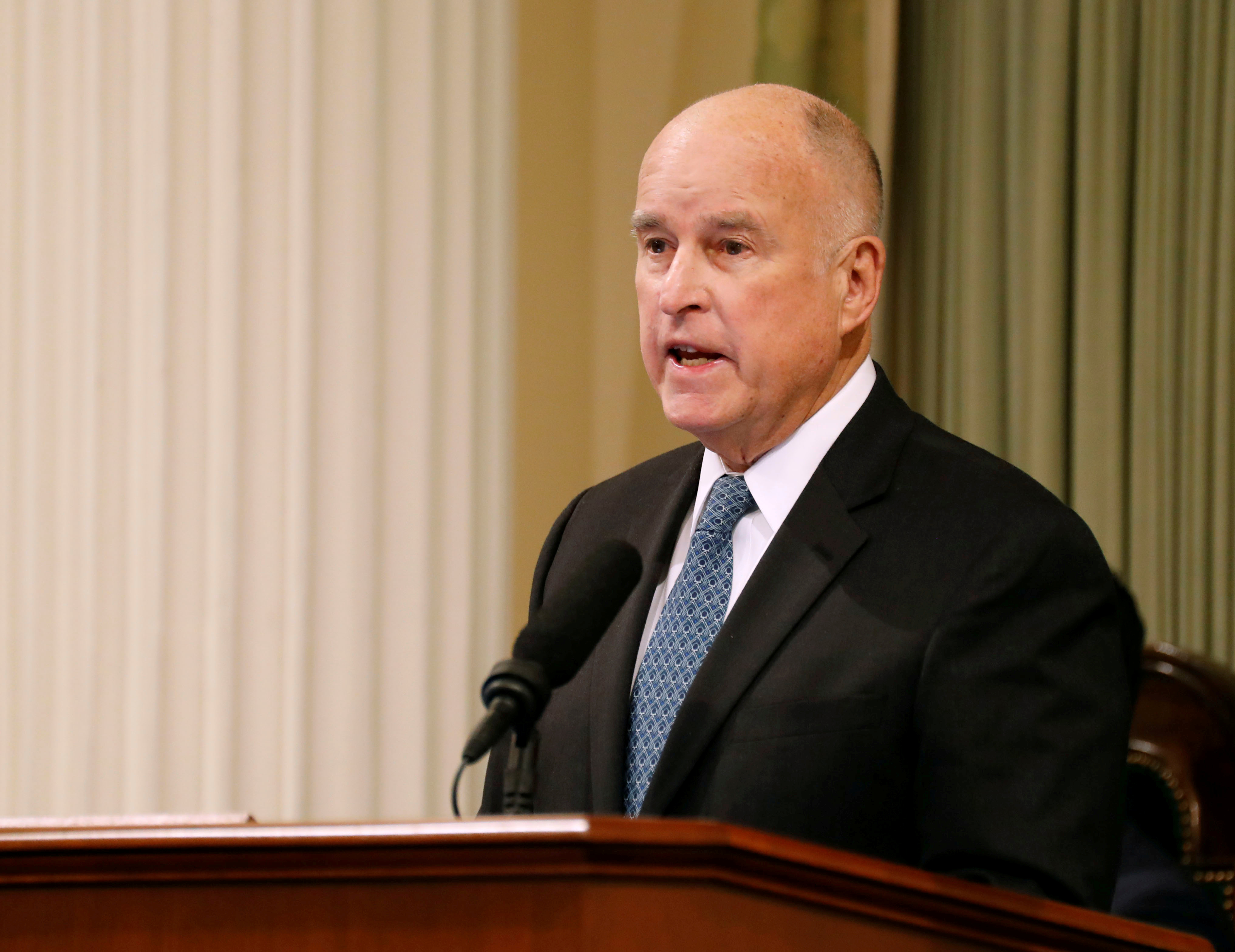 Former Governor Jerry Brown stands at a podium.