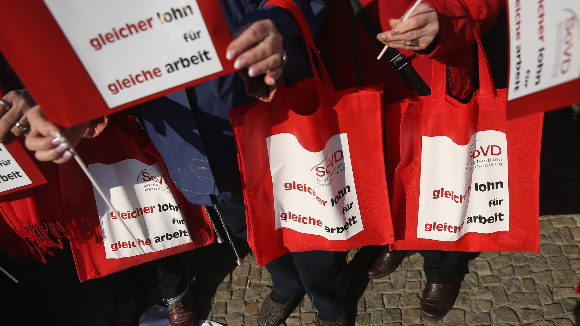 "Women hold bags and signs that read: ""Same pay for same work"" at a rally for equal pay in Berlin, Germany, 2015."
