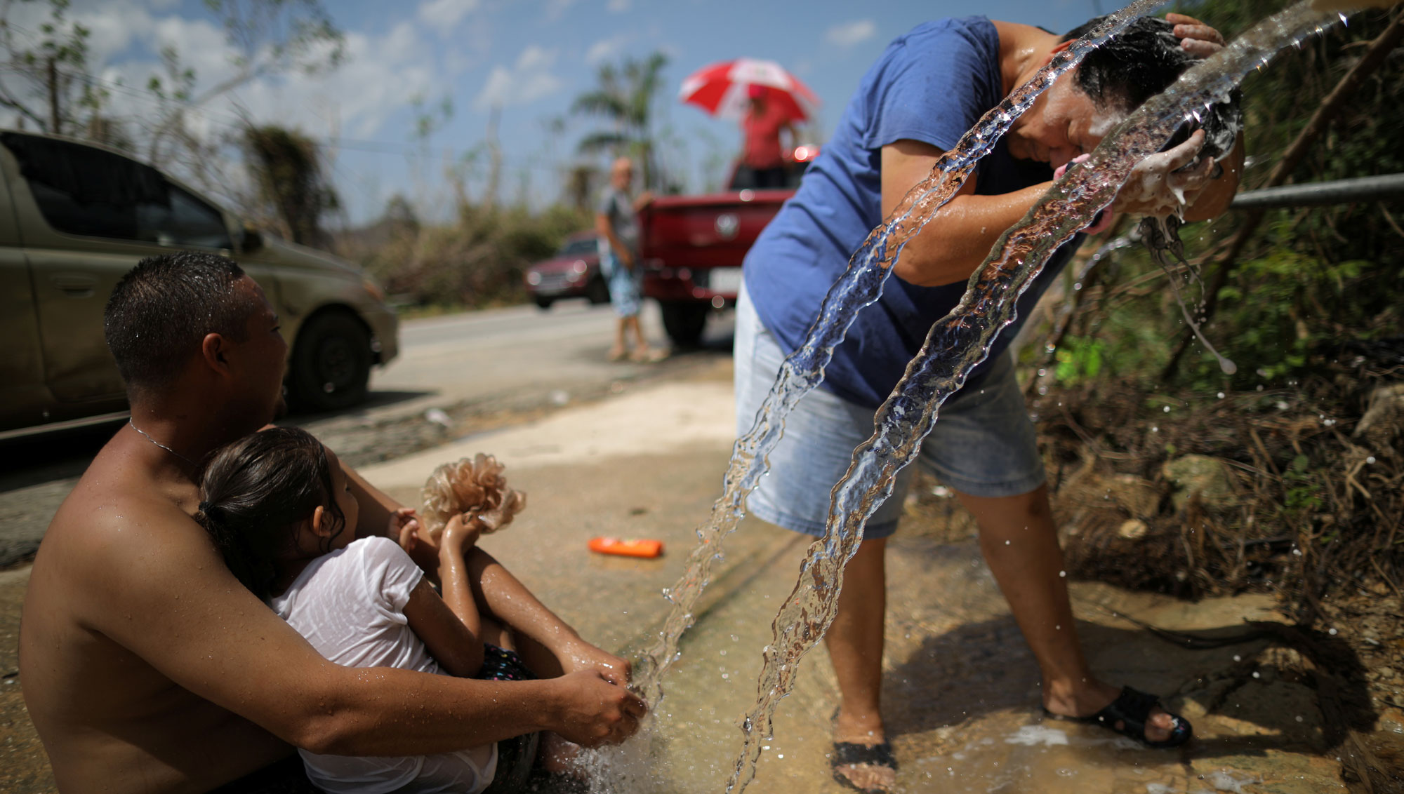 Water falls from a pipe onto the street. A woman in the background is bent at the waist and washes her hair in the running water, while a man holds a child and watches the woman.