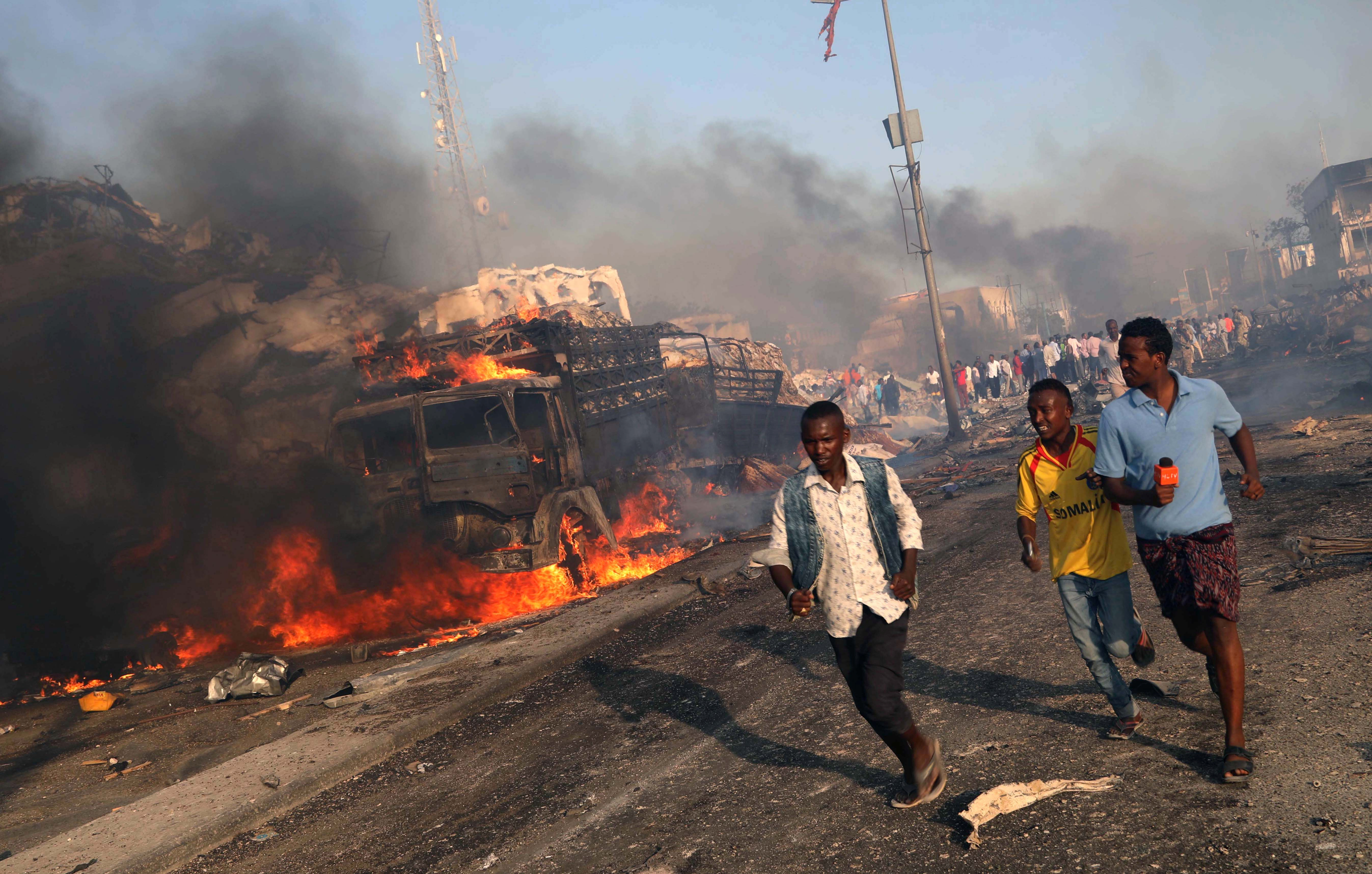 Civilians evacuate from the scene of an explosion in the Hodan district of Mogadishu, Somalia.
