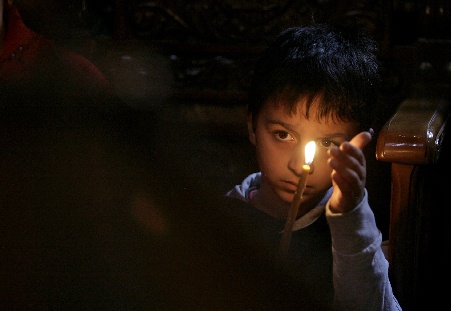 A child from the Roma community holds a candle at a church in Bucharest