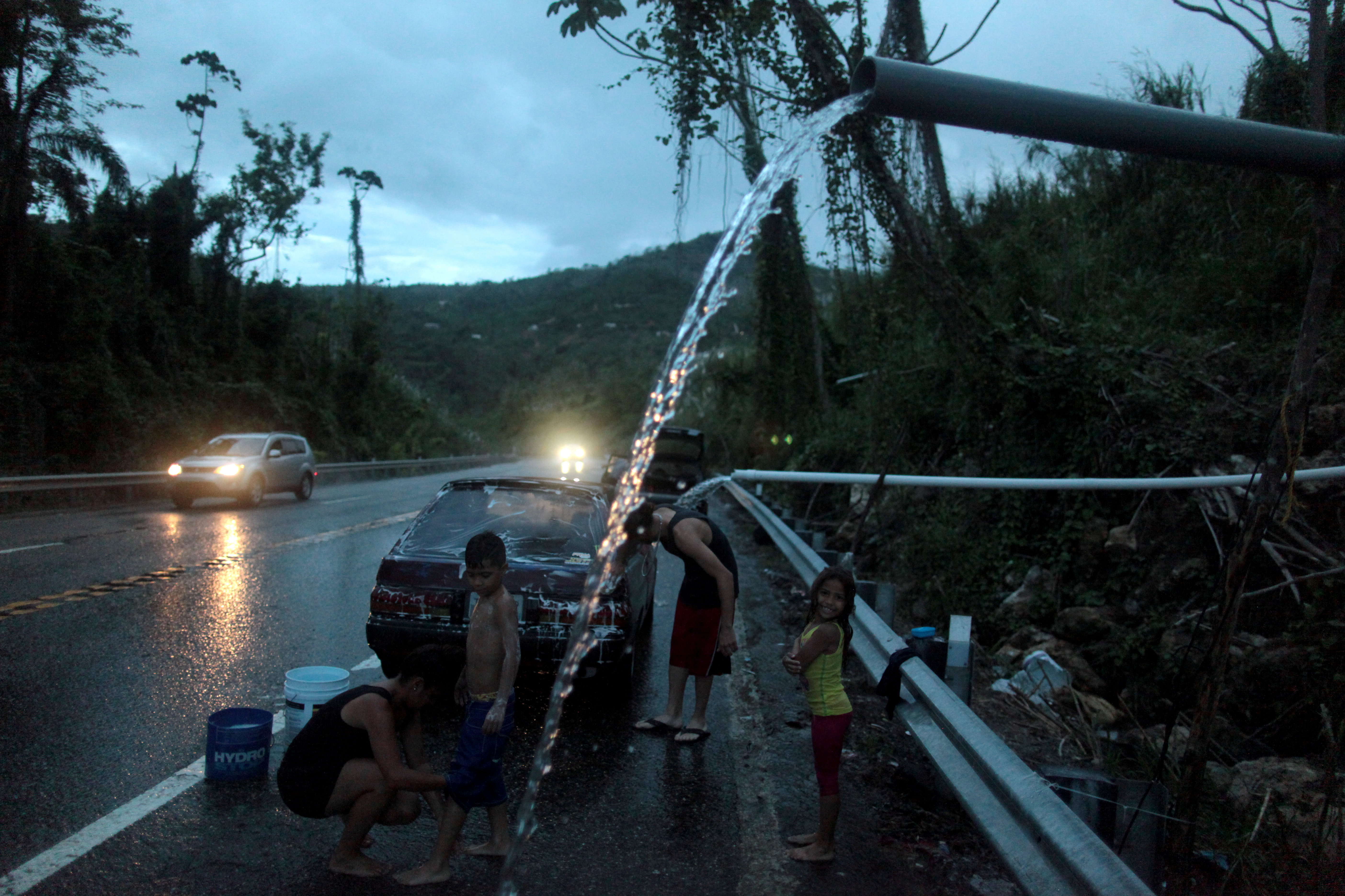 A family bathe and wash their car with mountain spring water after hurricane Maria hit the area in September, in Utuado, Puerto Rico.