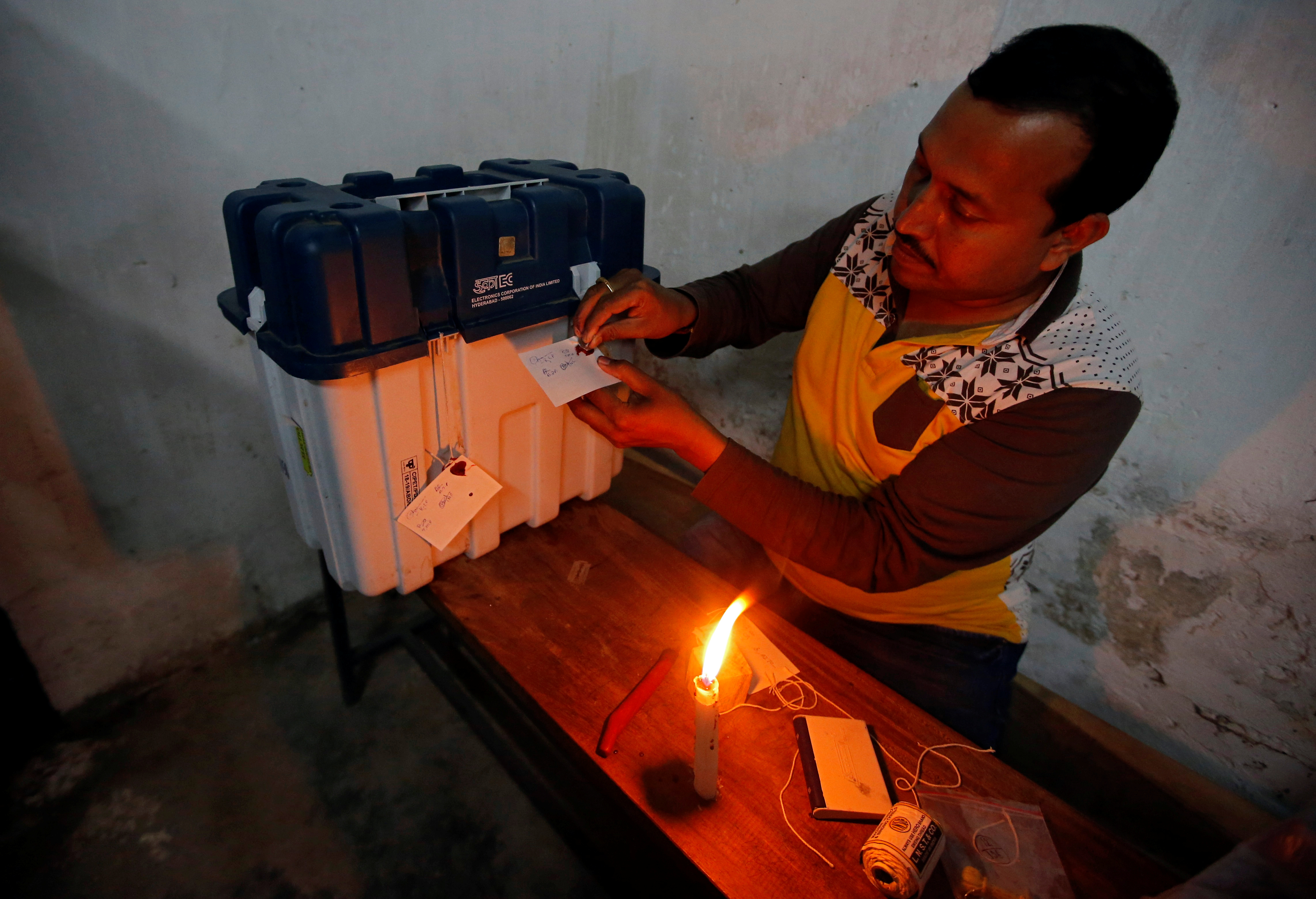 a voting official seals a ballot in india