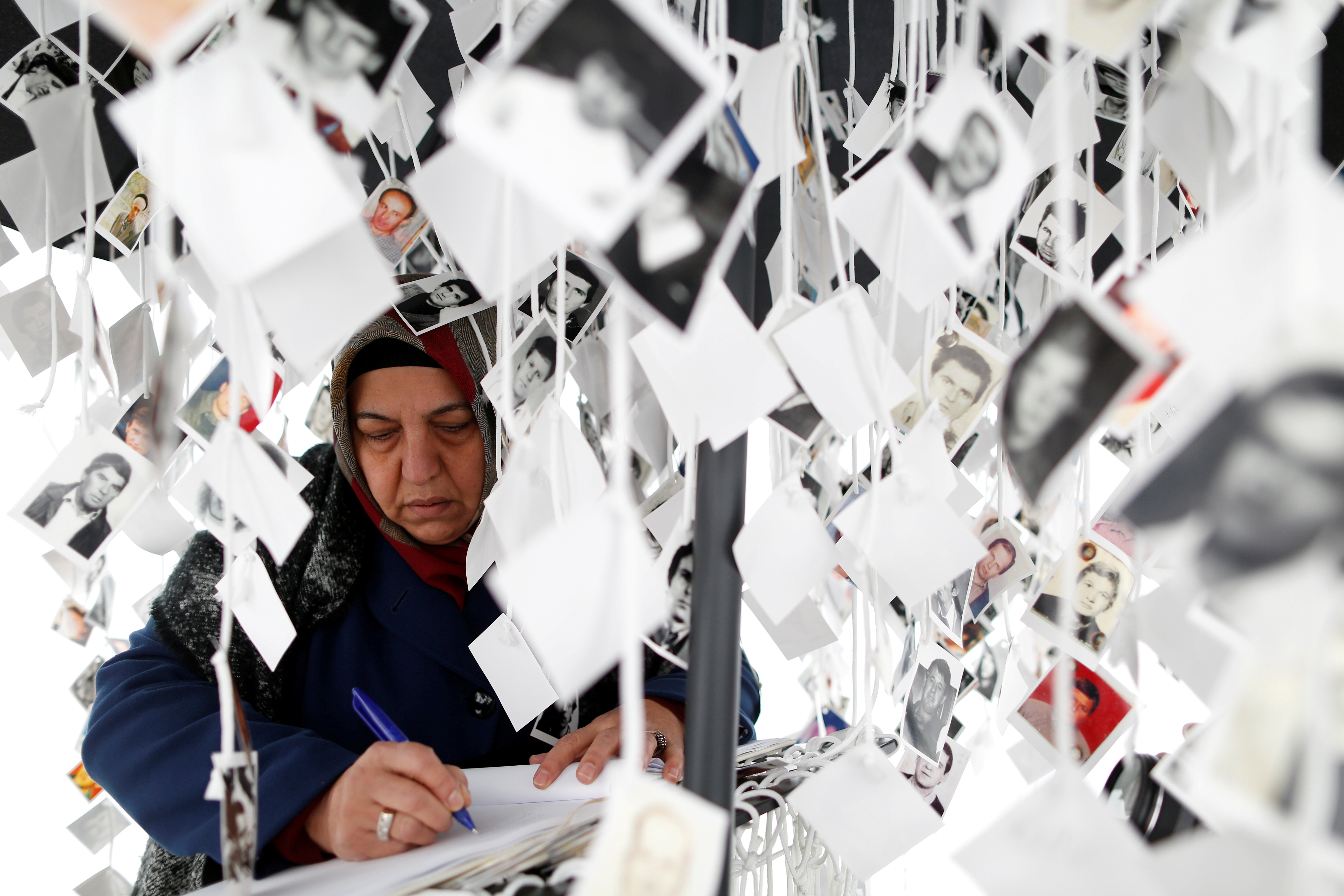 A woman writes in a book inside a traveling monument called 'Prijedor 92' outside the Yugoslav War Crimes Tribunal (ICTY