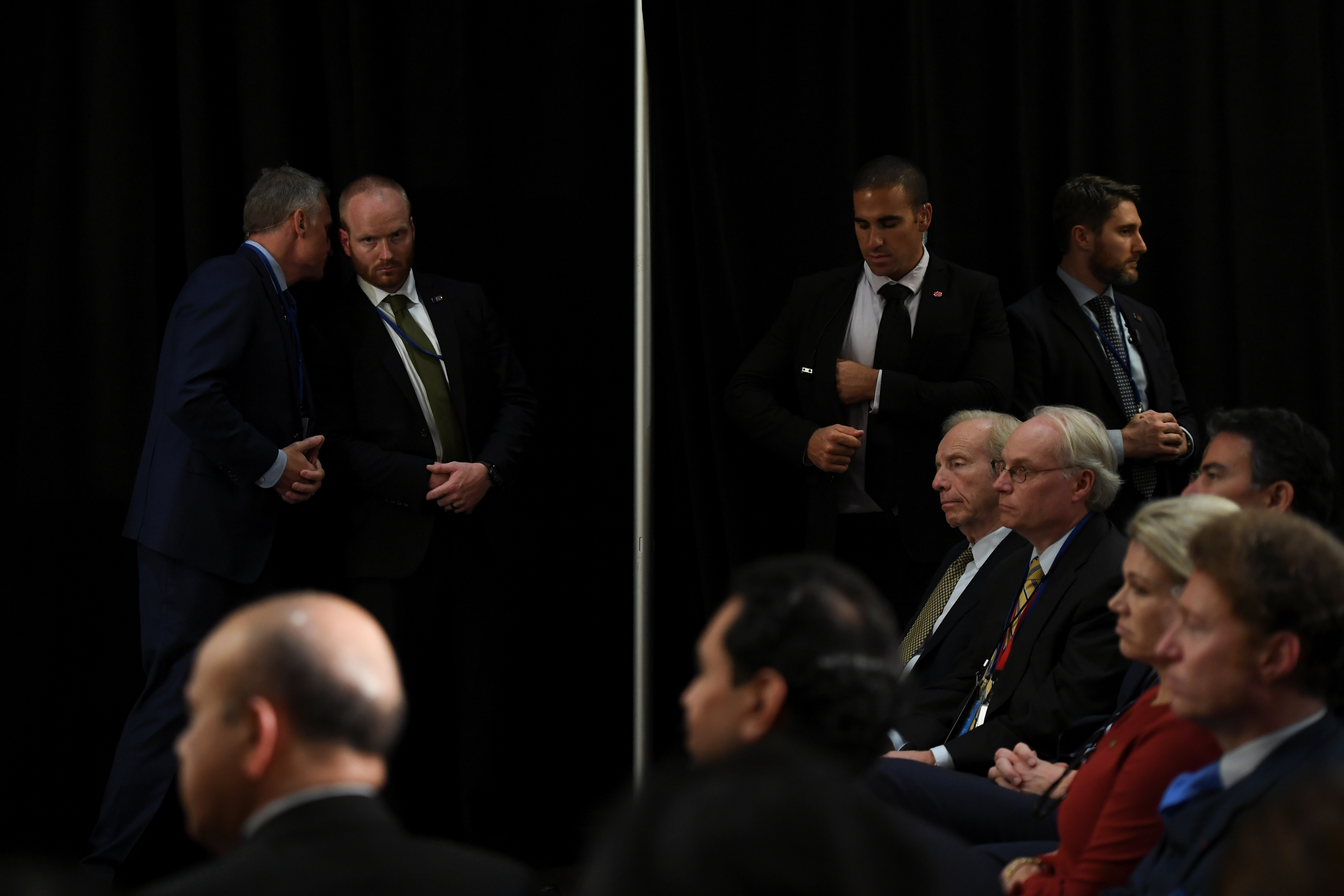 Several men in dark suits stand as others sit