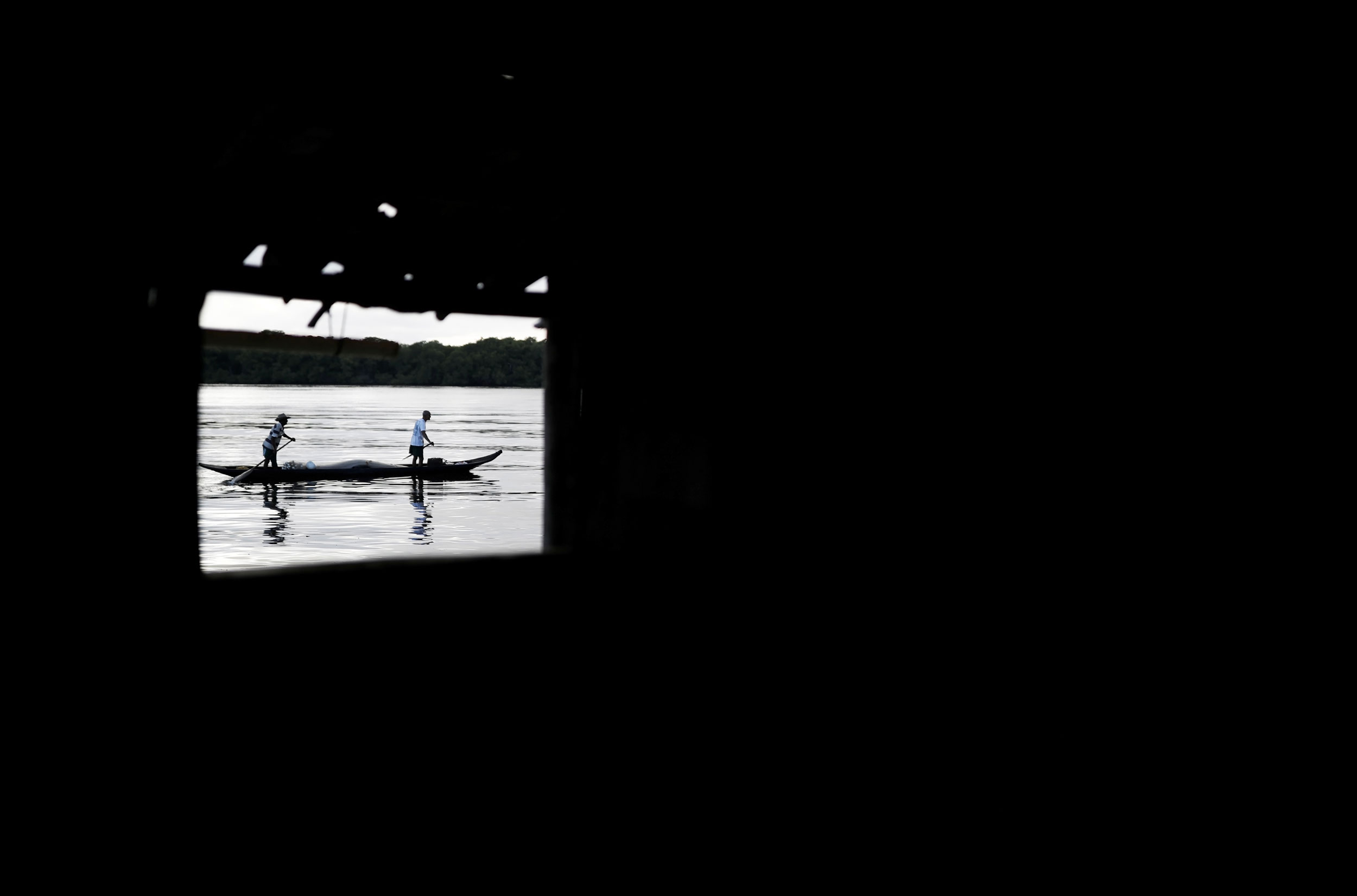 A dark photograph with a bright window showing people on a boat.