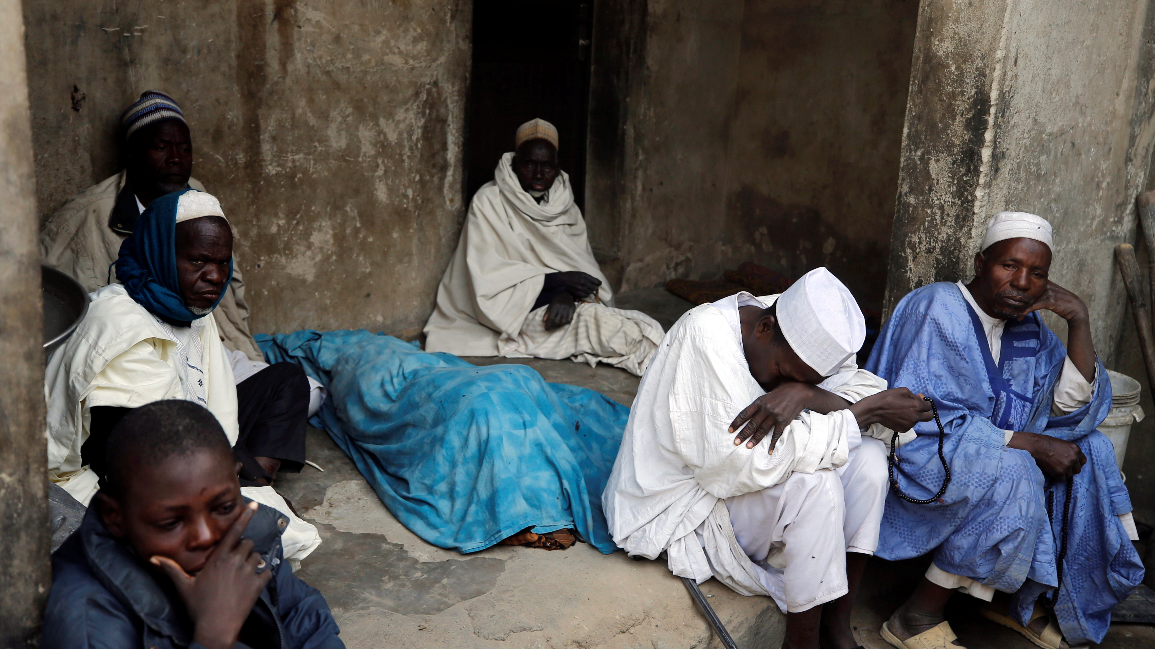 A family of men sit on a porch and cry with their heads down.