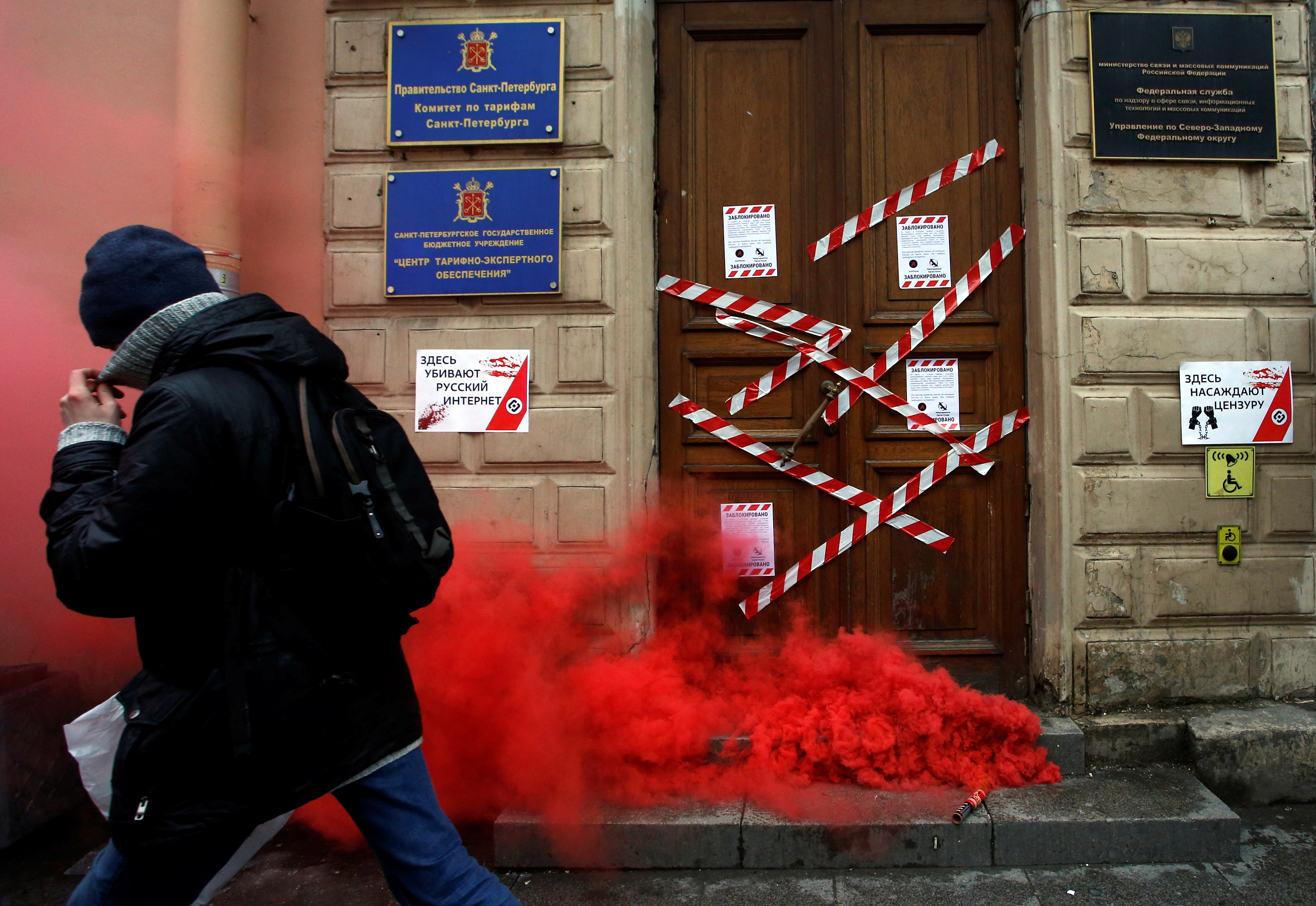 A protester walks away from a door with smoke in front of it.