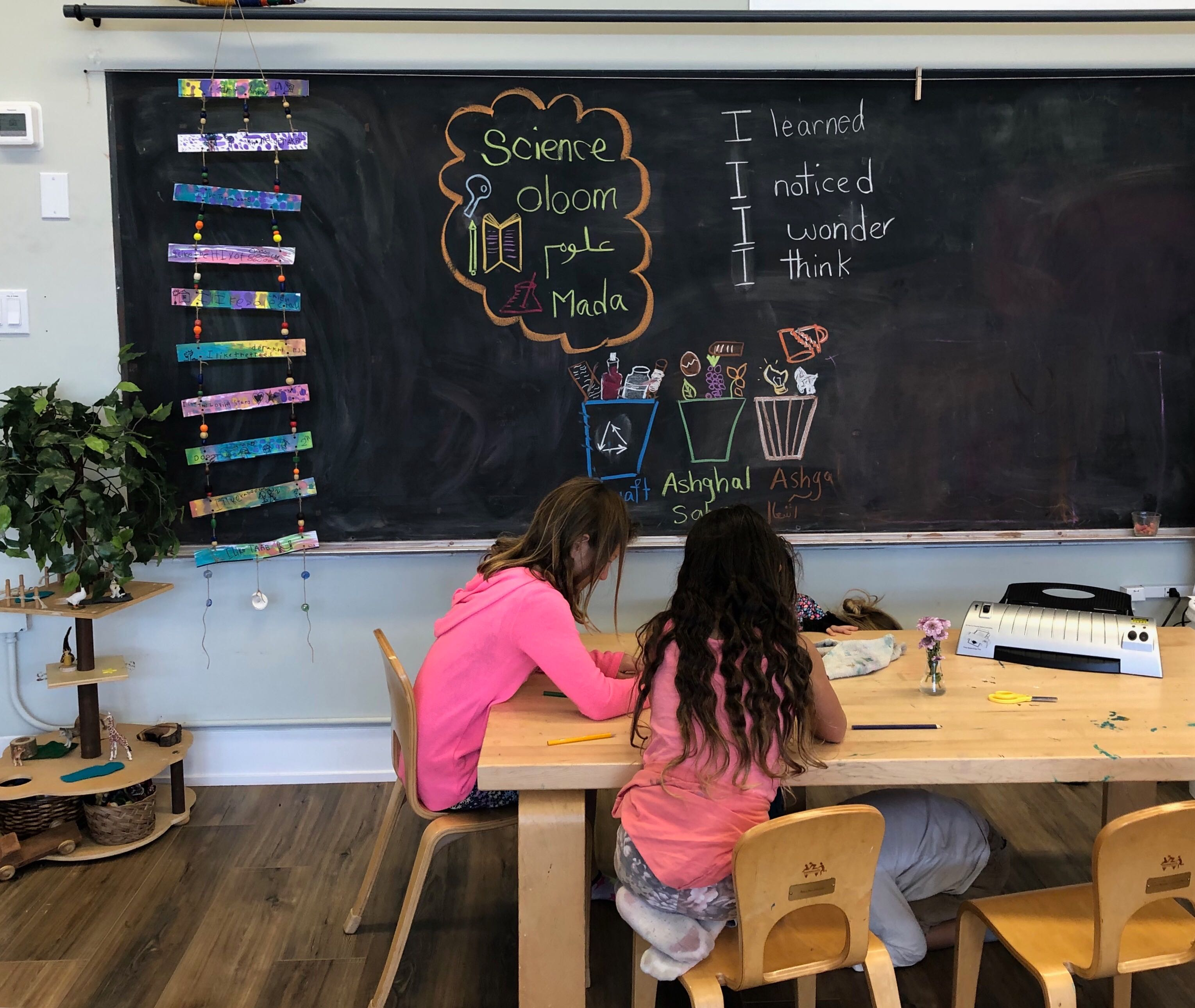 Two young girls sit a table in front of a chalkboard.